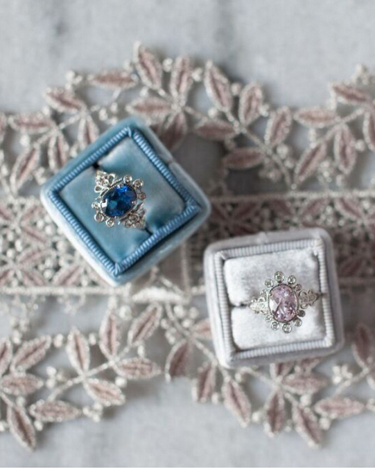 claire-pettibone-ring-collection-two-rings-in-boxes-on-lace-0915.jpg