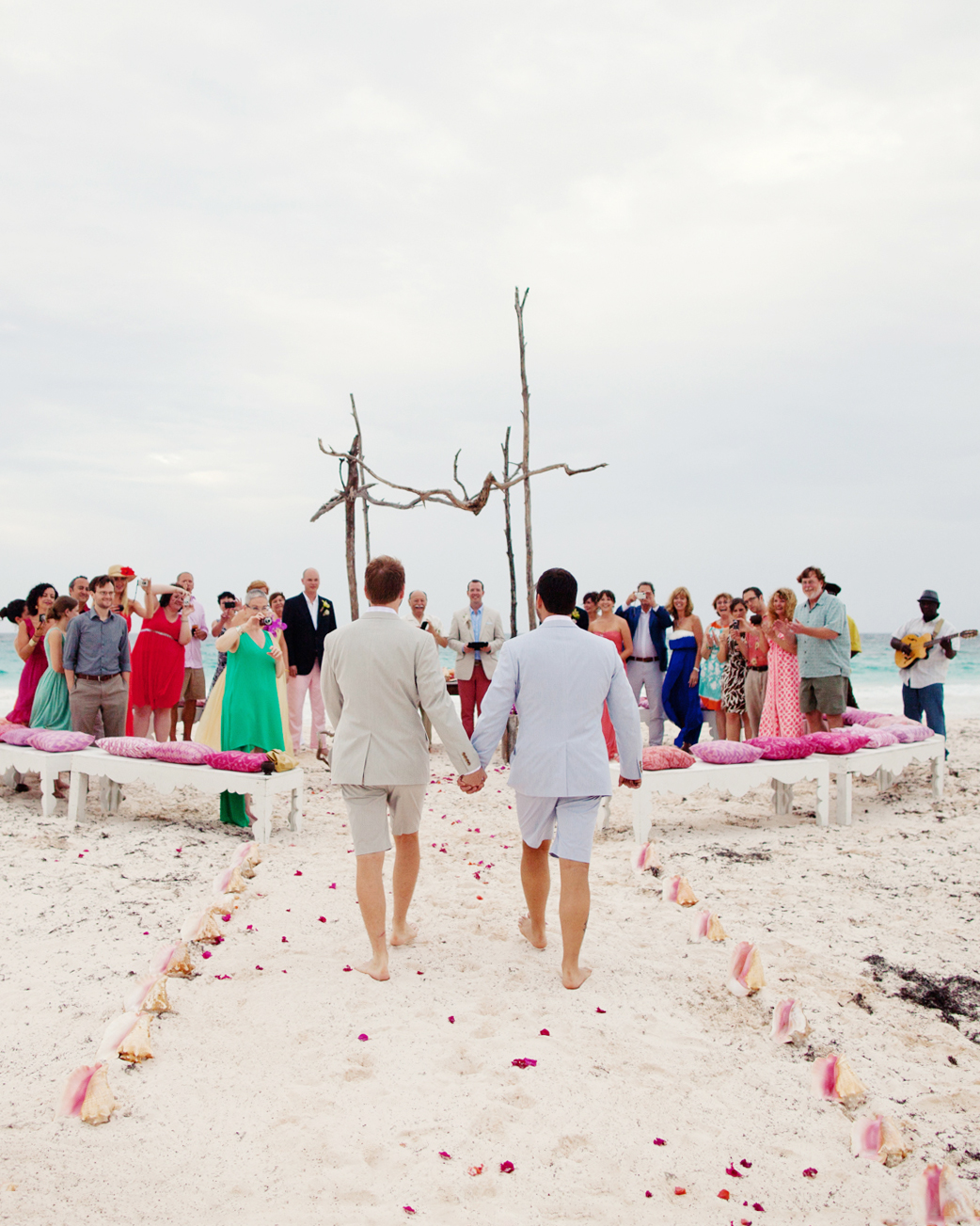 """Couples of every orientation are bending the rules to customize their ceremonies, so feel free to take a route less traveled to the altar. You can ask a person of mutual importance to escort the two of you on each arm. Or walk one behind the other with your respective parents, though you'll still have to figure out who goes first (rock-paper-scissors?). If neither one of you is being """"given away,""""proceed hand-in-hand. Or consider an alternate floor plan—dual aisles. Dividing the seating into three sections, separated by two aisles, allows you each a path to the altar. Just keep in mind: Separate, simultaneous routes require a second photographer."""