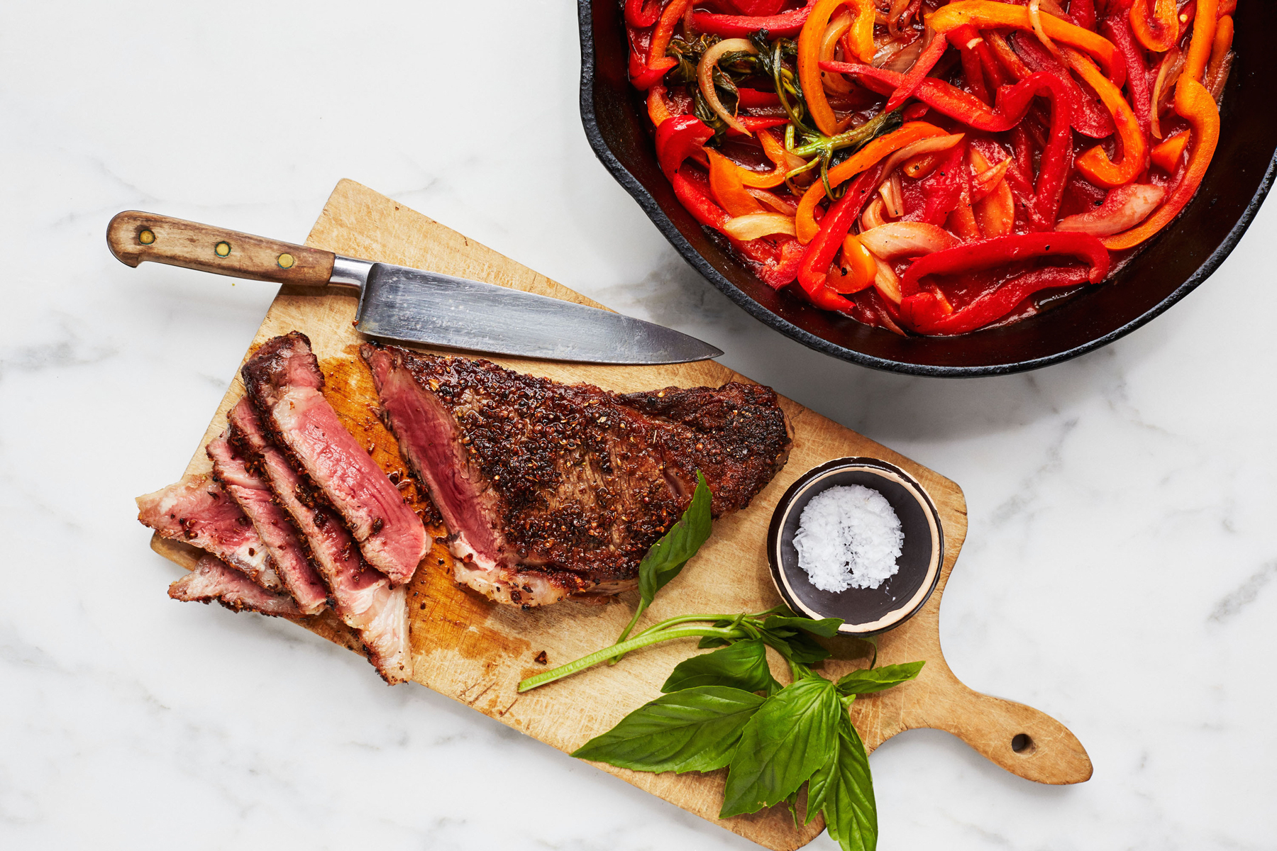 seared strip steaks with braised peppers and onions