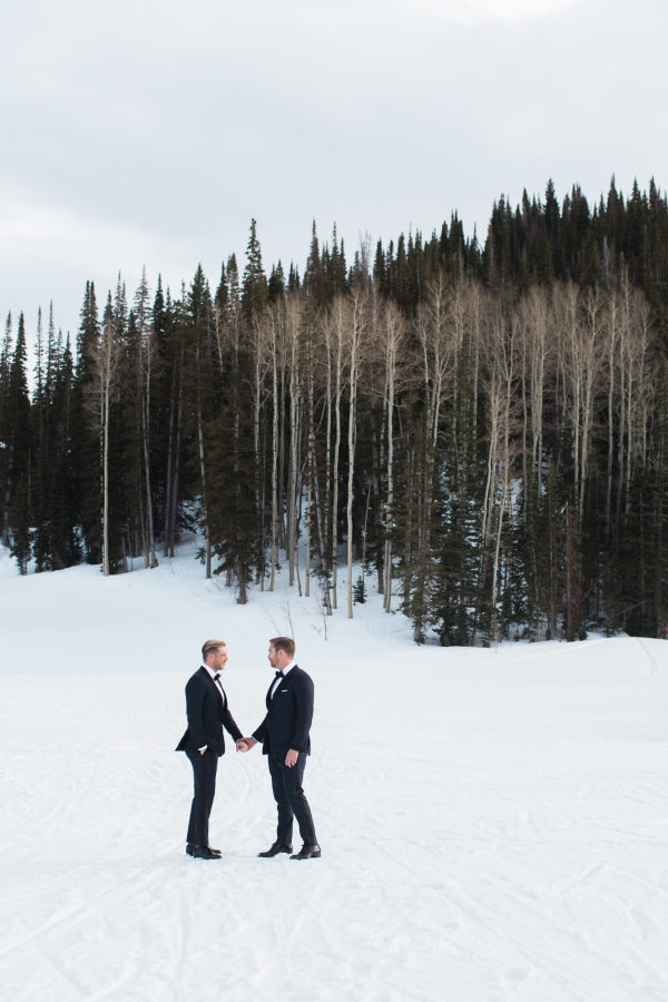 couple standing by snowy woods