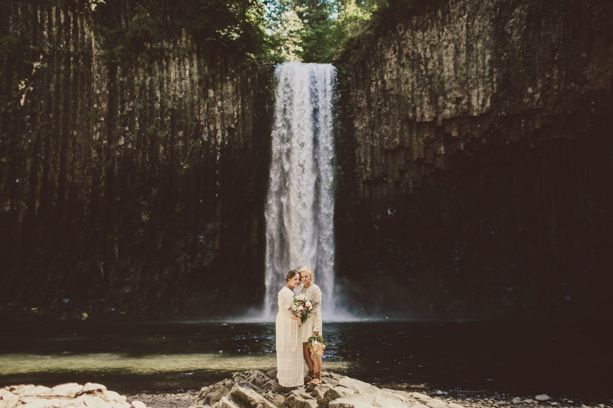 couple standing in front of waterfall