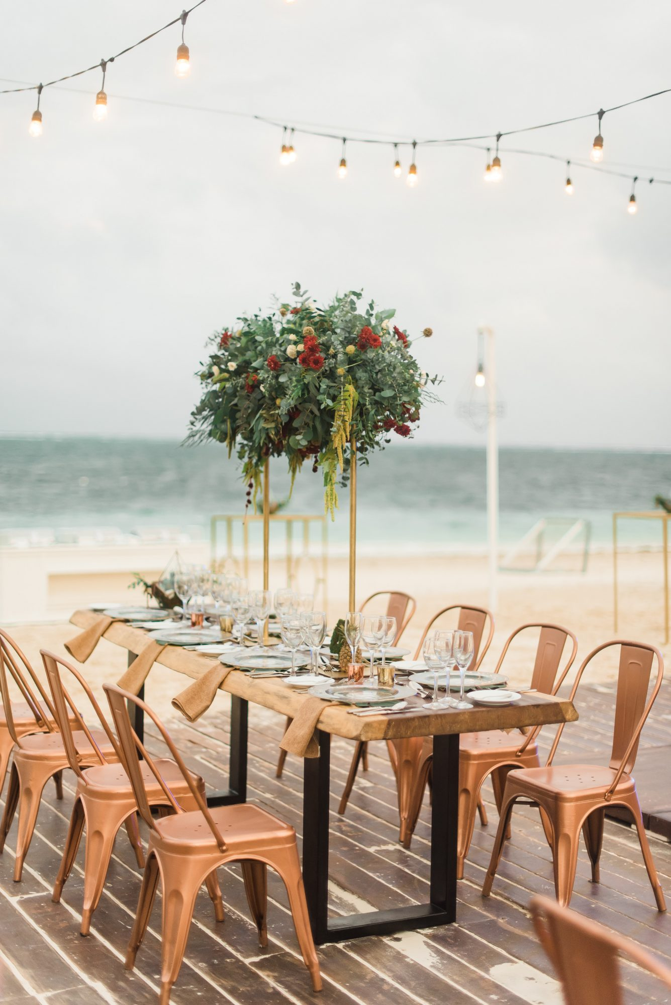 tall centerpiece with greenery and red flowers
