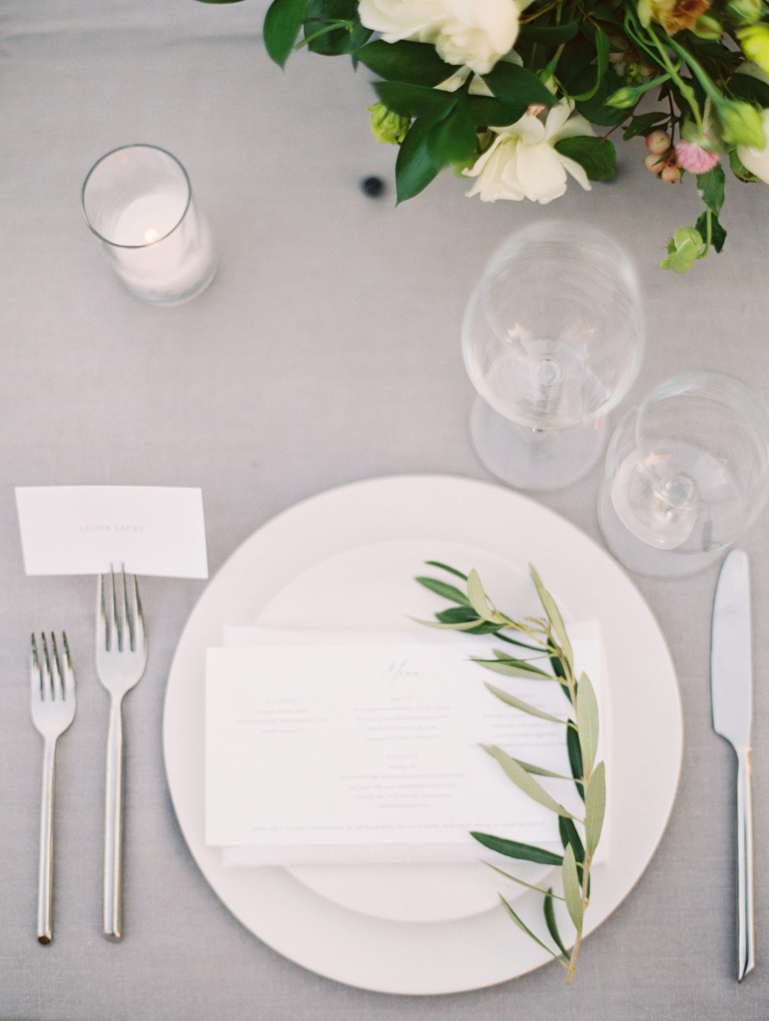 white and gray table setting with greenery