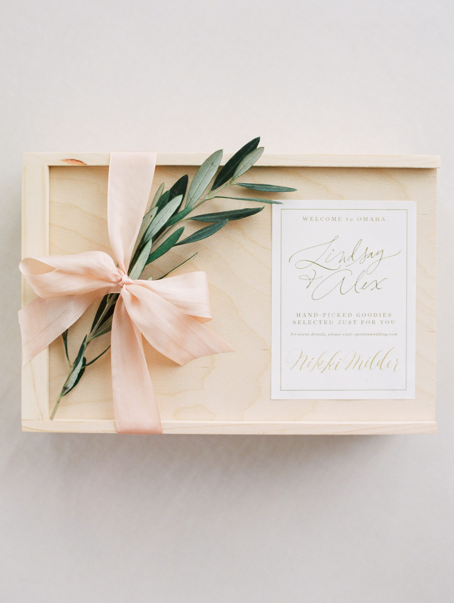 favor box with greenery and pink ribbon