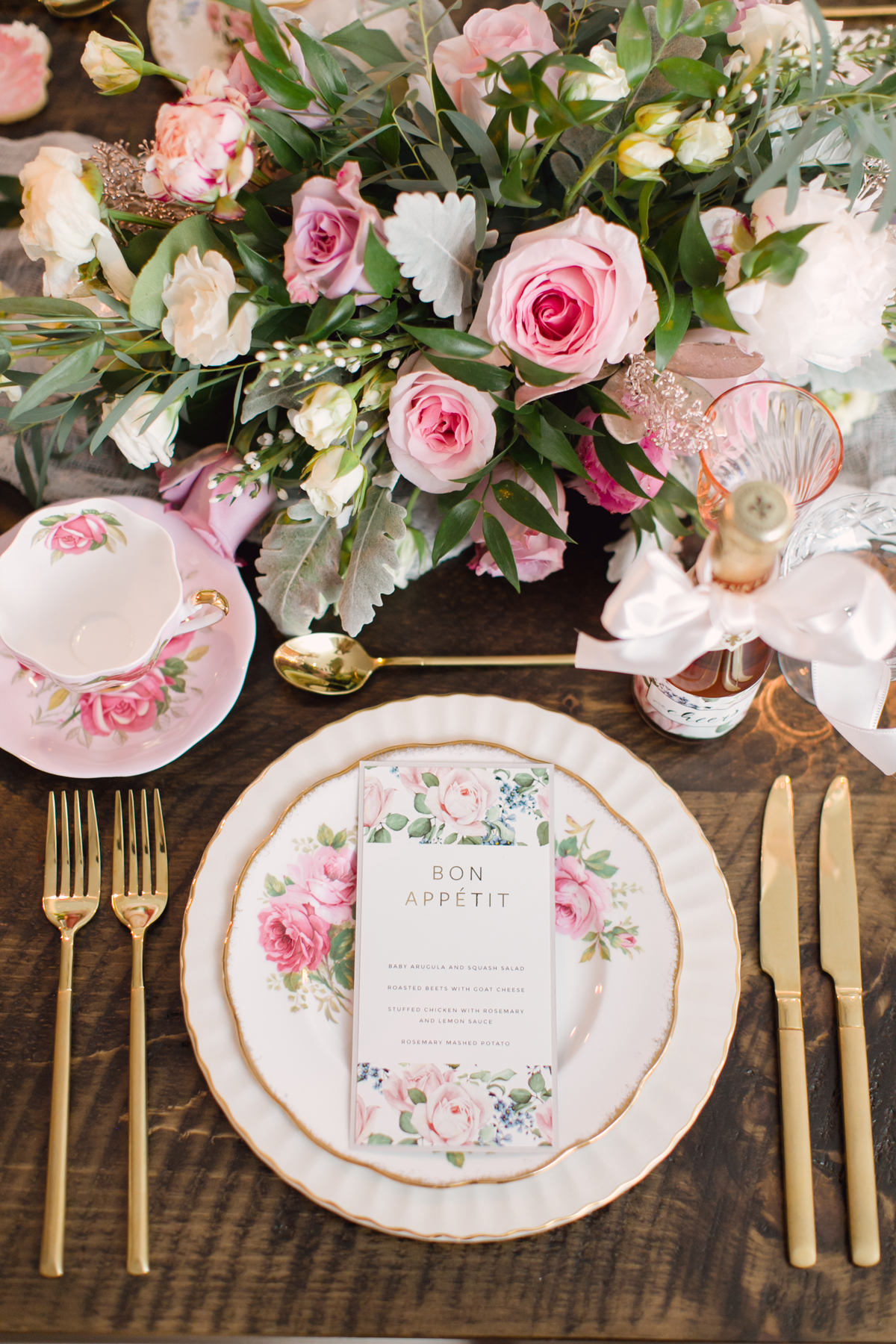 pink floral placesetting accents on white and gold tableware