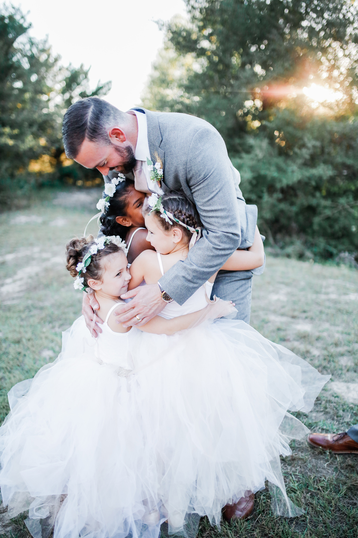 groom hugging flower girls
