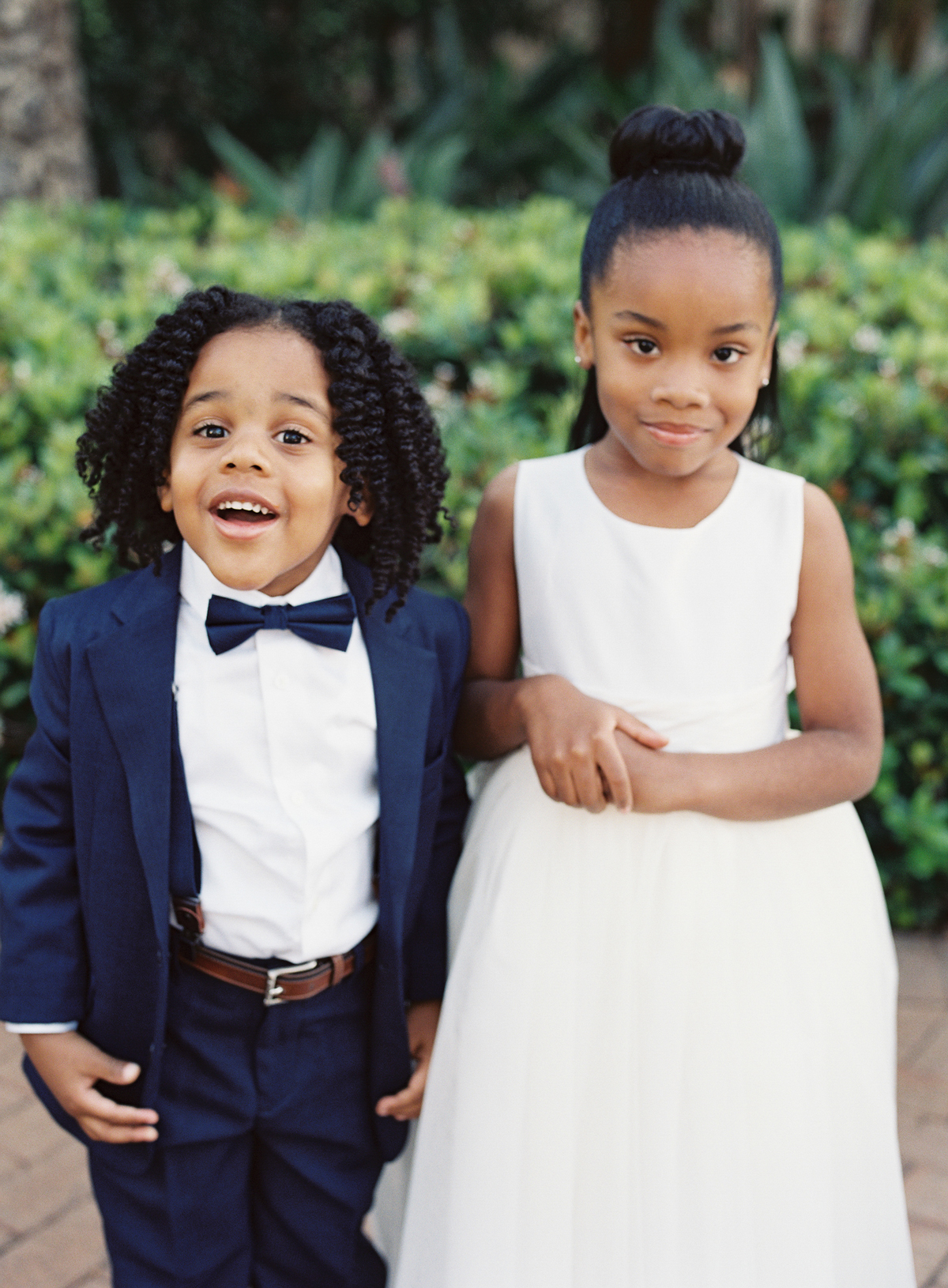 smiling ring bearer and serious flower girl