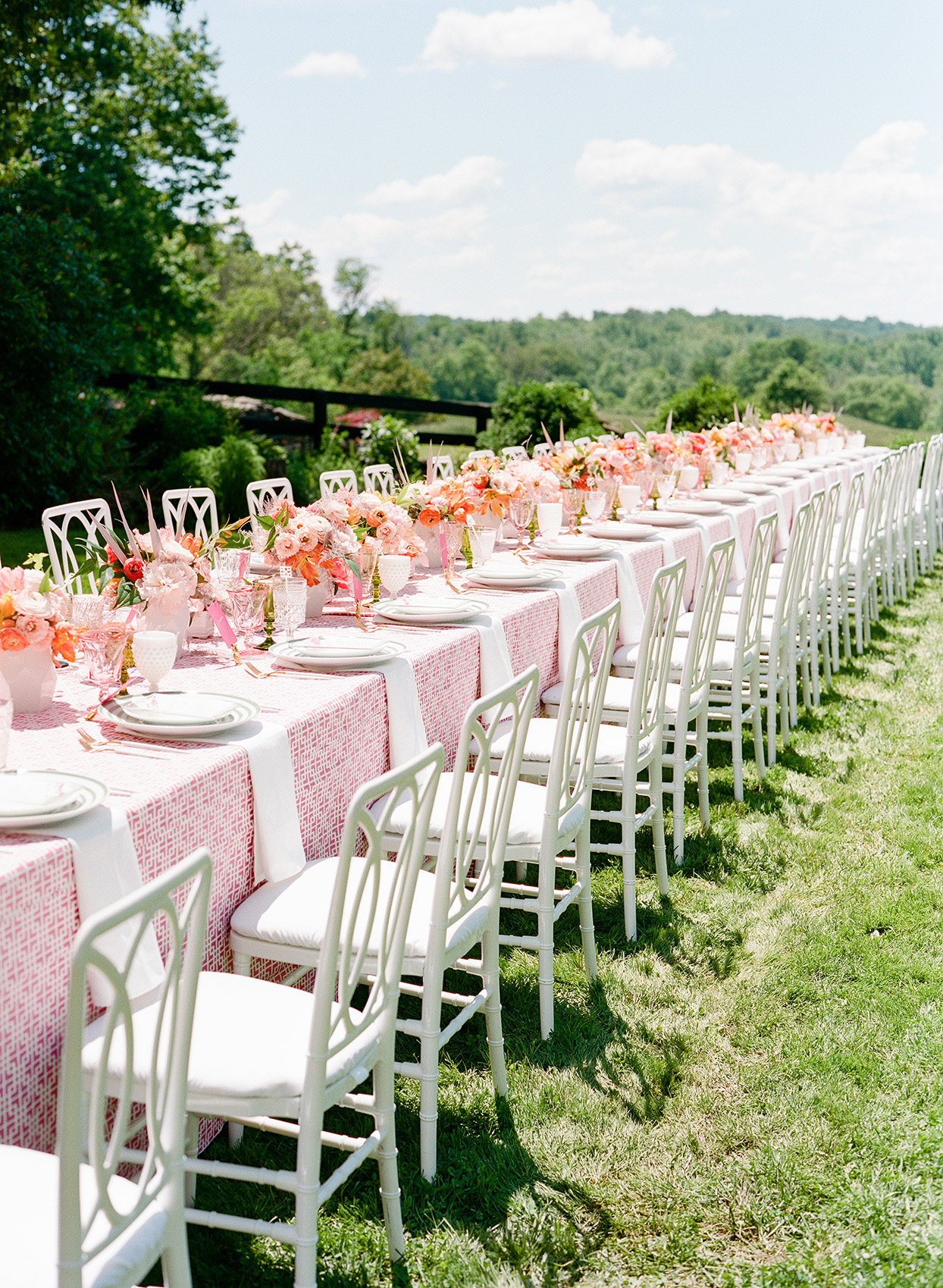 long wedding table with pink runner and flowers