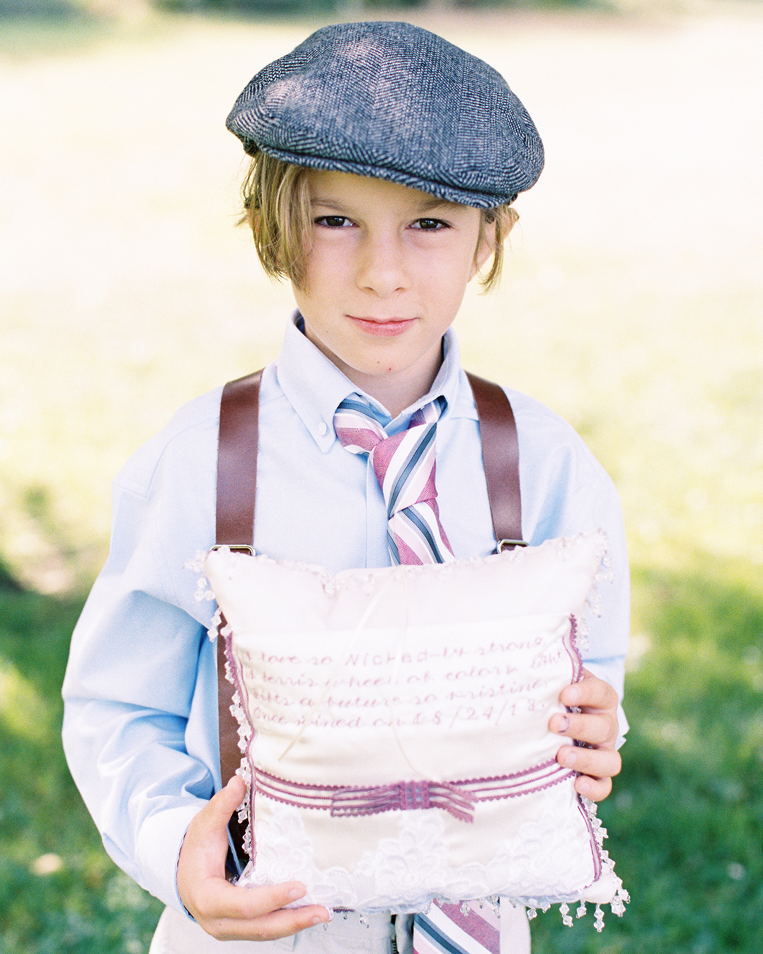 ring bearer in beret holding quote pillow at wedding