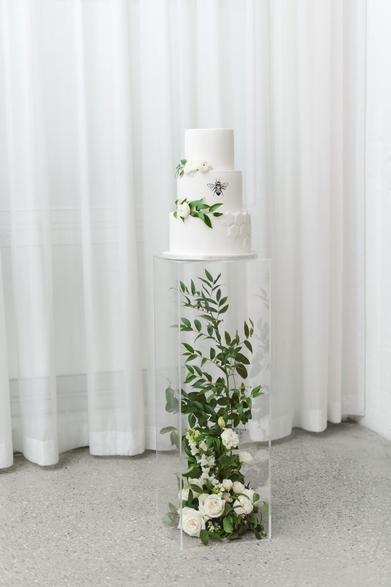 lucite pedestal containing greenery and white roses displaying bee themed wedding cake
