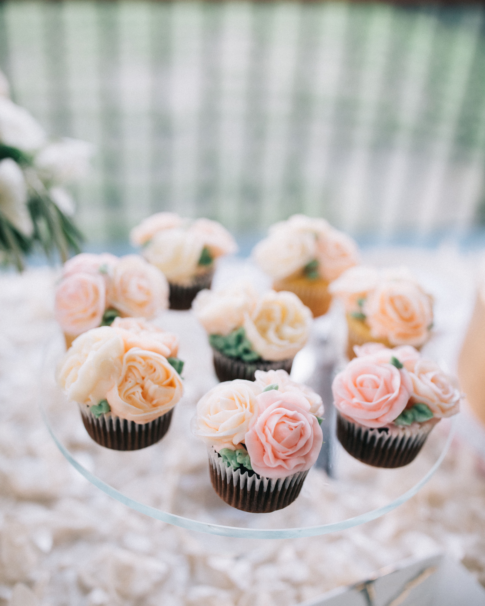 mini chocolate cupcakes with peach and pink frosted flowers