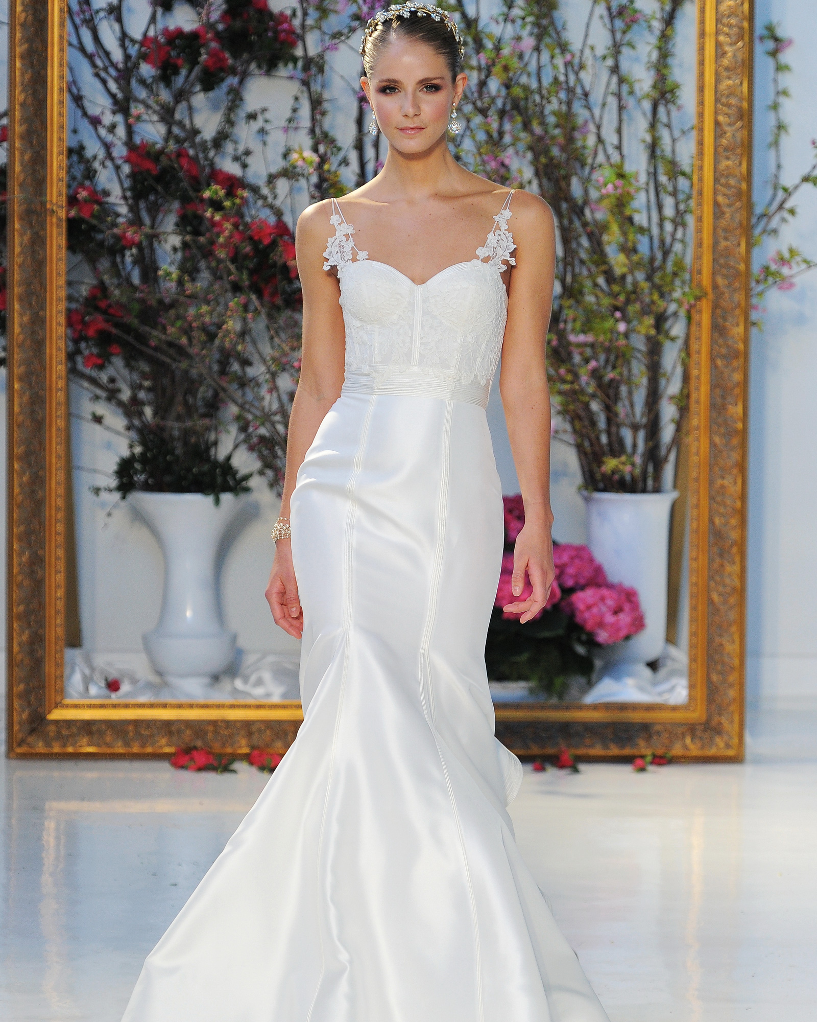 """Always a favorite for the classic bride, Anne Barge pulled out all the stops with her Spring 2017 collection, which she says was inspired by """"nature's ethereal transition,"""" or """"the awakening of spring gardens, still covered in frost, petals only peeking."""" We're loving the intricate lace detailing and shoulder and neck adornments. Simple and refined, the elegant dresses truly are a perfect blend of contemporary and classic, but with a bit of boho, too.                             """"Chandler""""                             Corset bodice of lace and soutache with mermaid Kalika skirt and linear seaming with flutter train."""