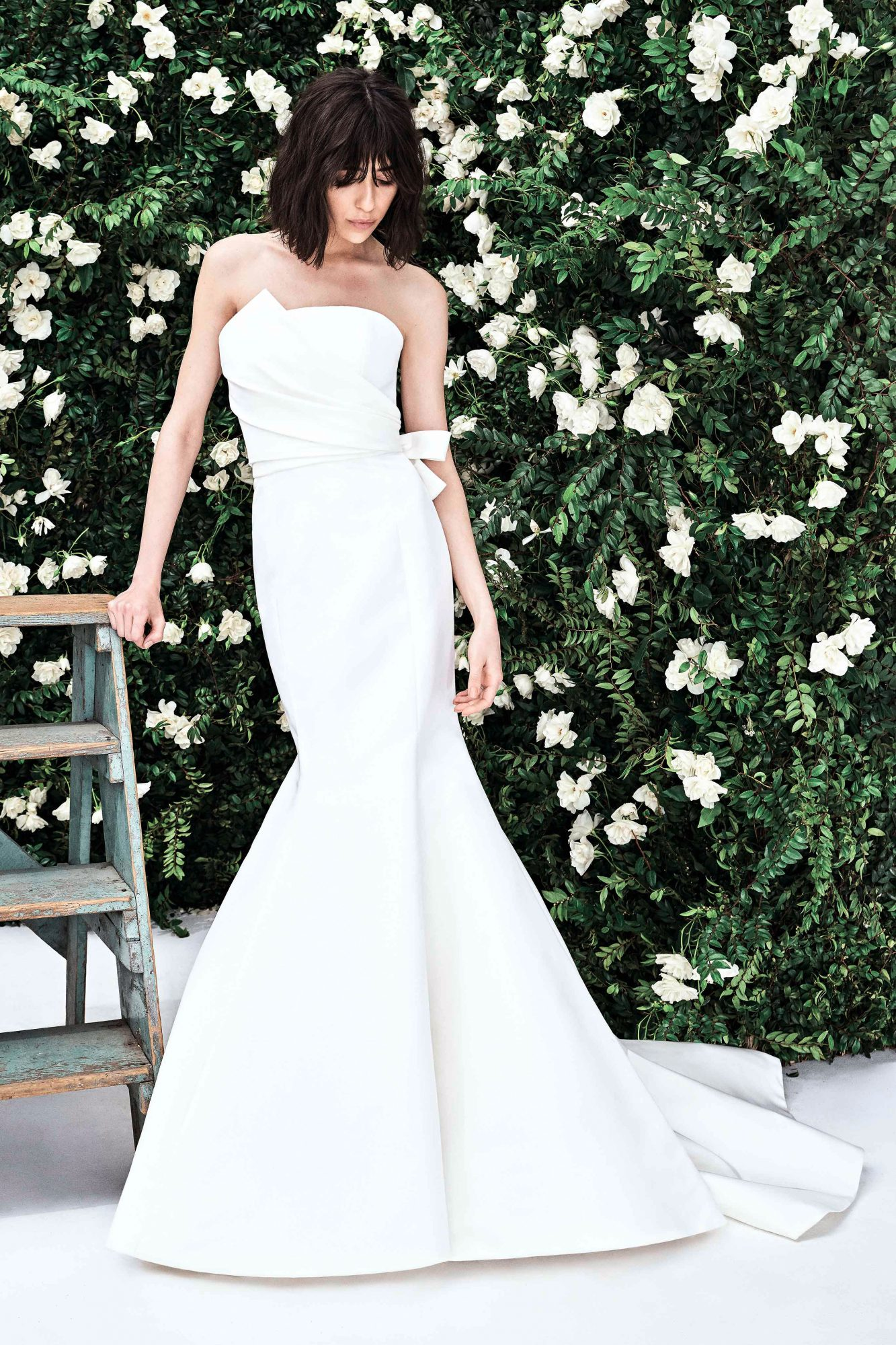 Strapless mermaid wedding dress with asymmetrical draped bodice and bow at waist