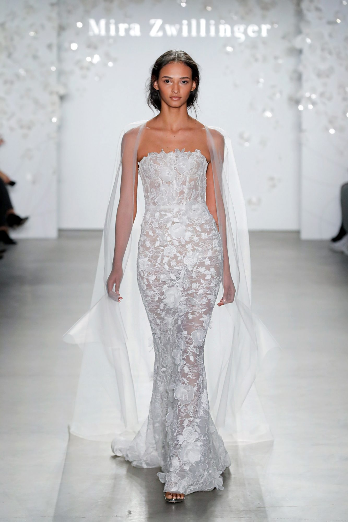 Strapless mermaid wedding dress with 3D floral appliqués and open back, wornwith cape