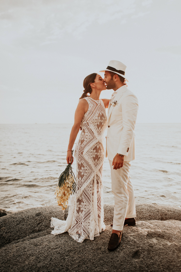 beach wedding dresses bride and groom kissing on rock