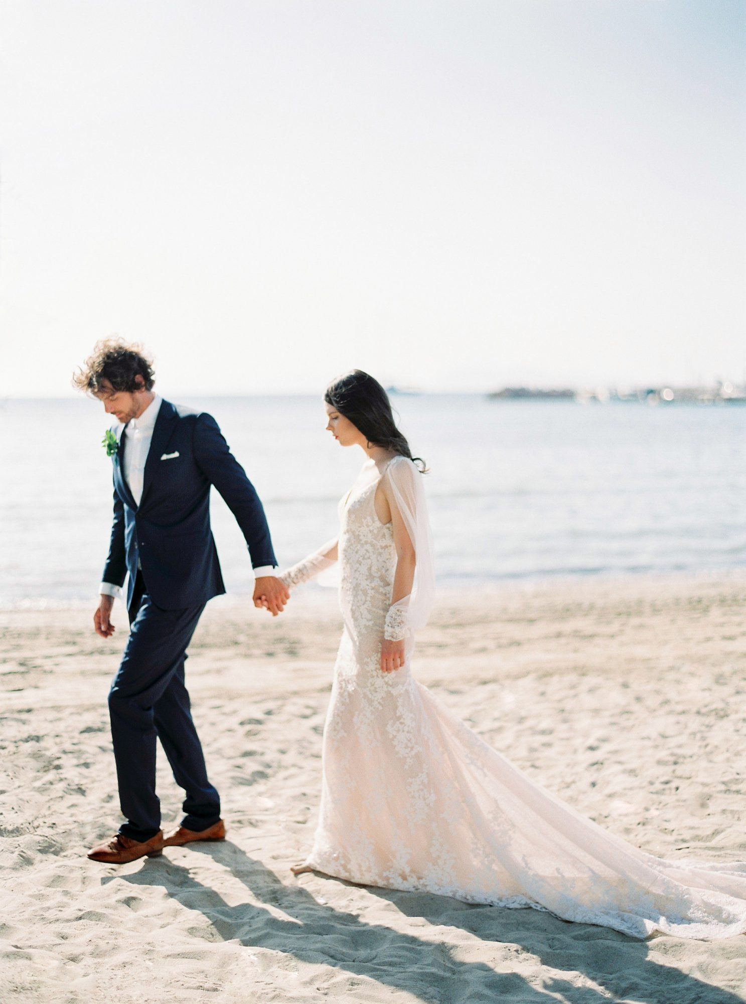 beach wedding dresses bride and groom holding hands on waters edge
