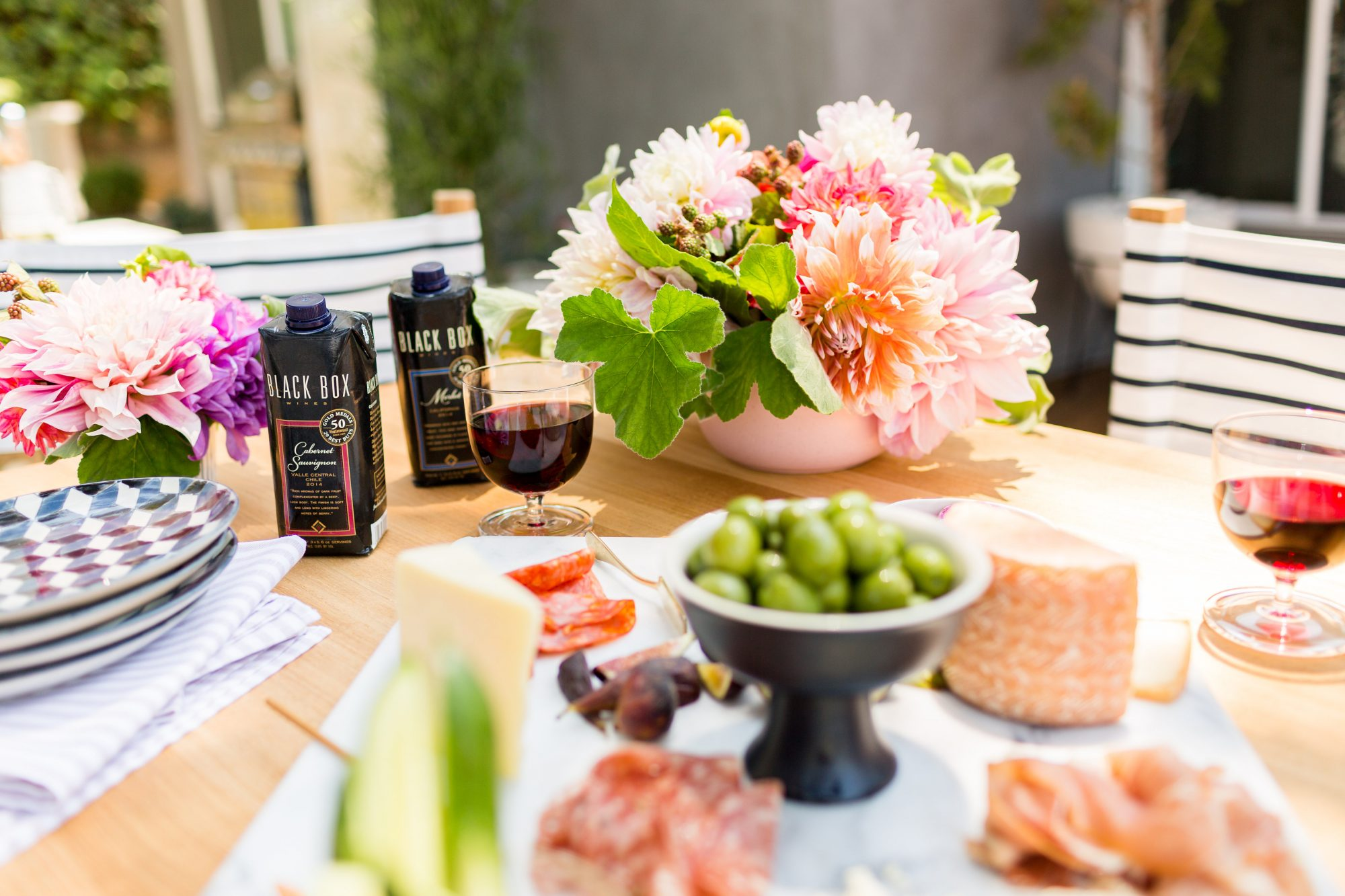 A bridal shower table by Emily Henderson, complete with flowers, wine, and charcuterie tray