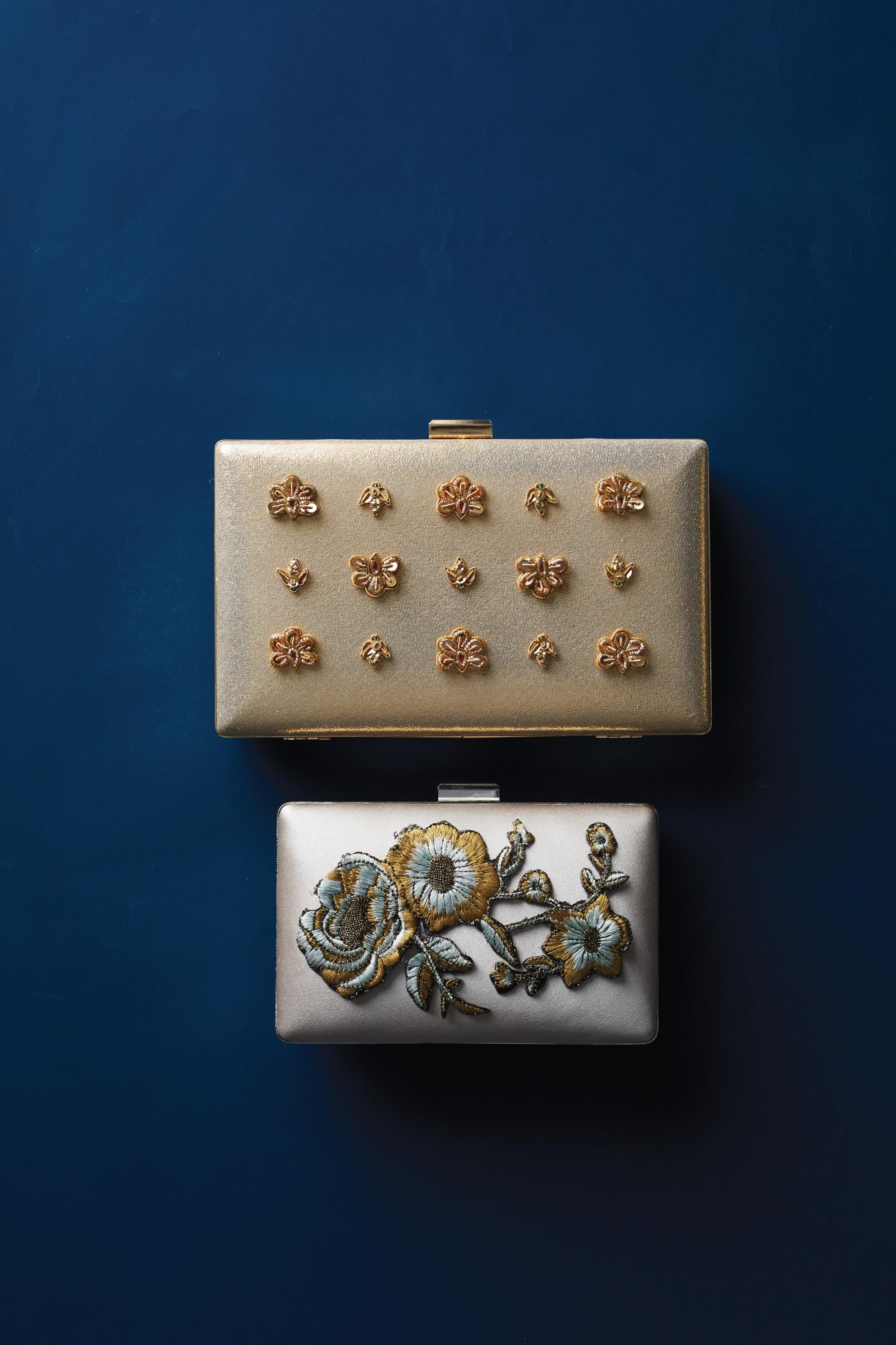 Grab a uniform batch of simple clutches or mix and match a few (we chose a minaudières and pillbox clutches). Then, spice up the bland design with custom appliqués of your choice. If you're extra proud of your handiwork, have your 'maids hold them on the big day!