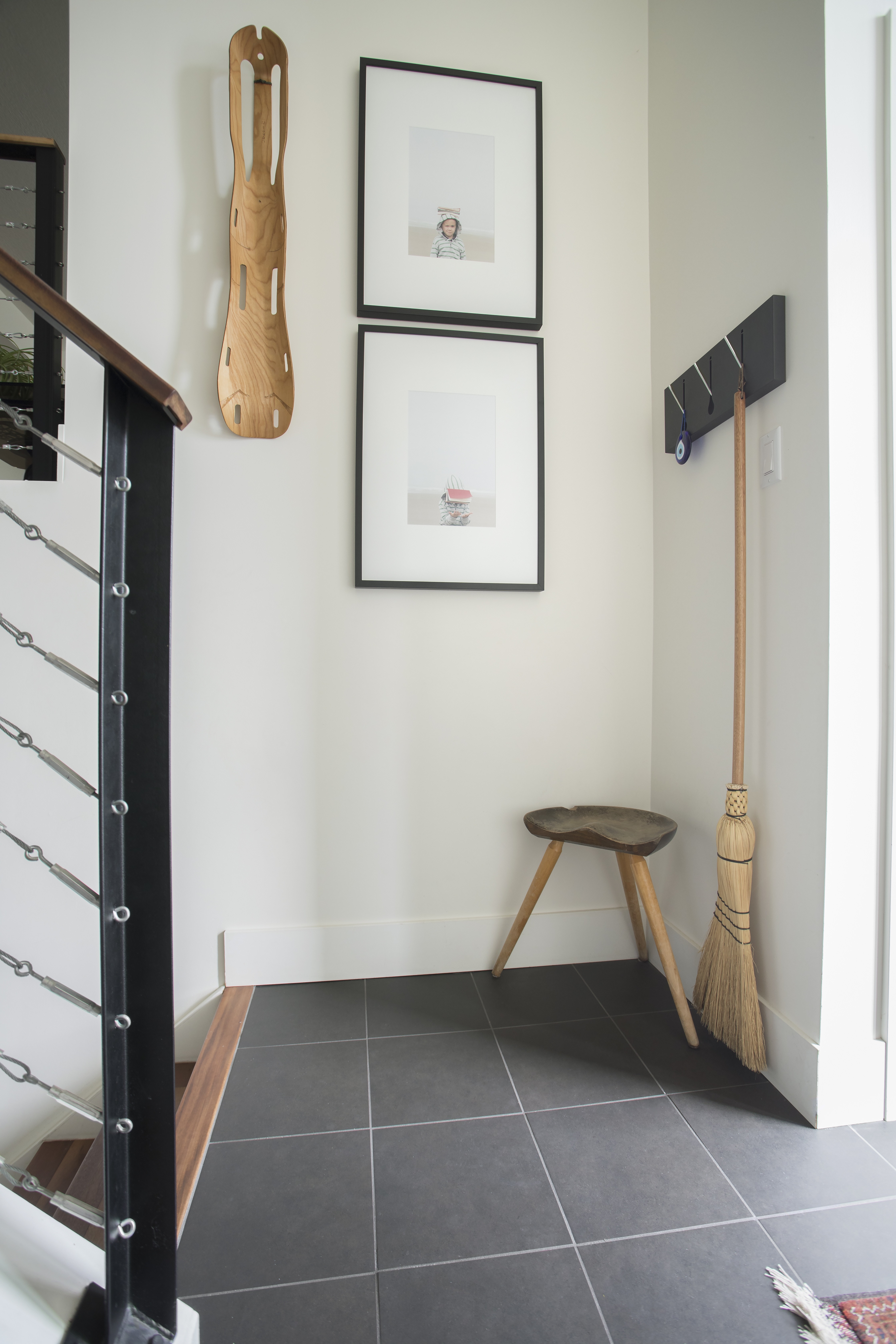 hallway with picture frames and broom hook