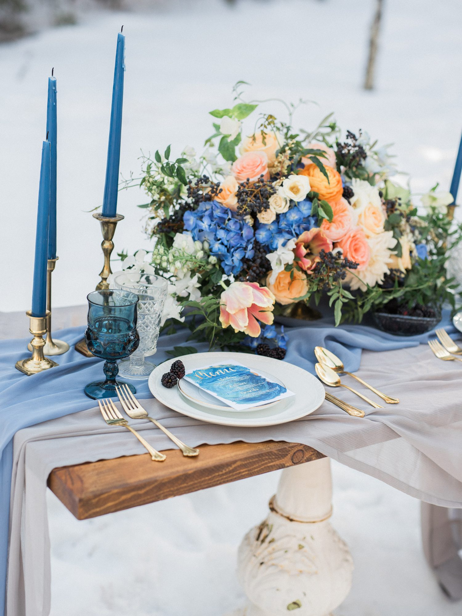 centerpiece with blue flowers and orange garden roses