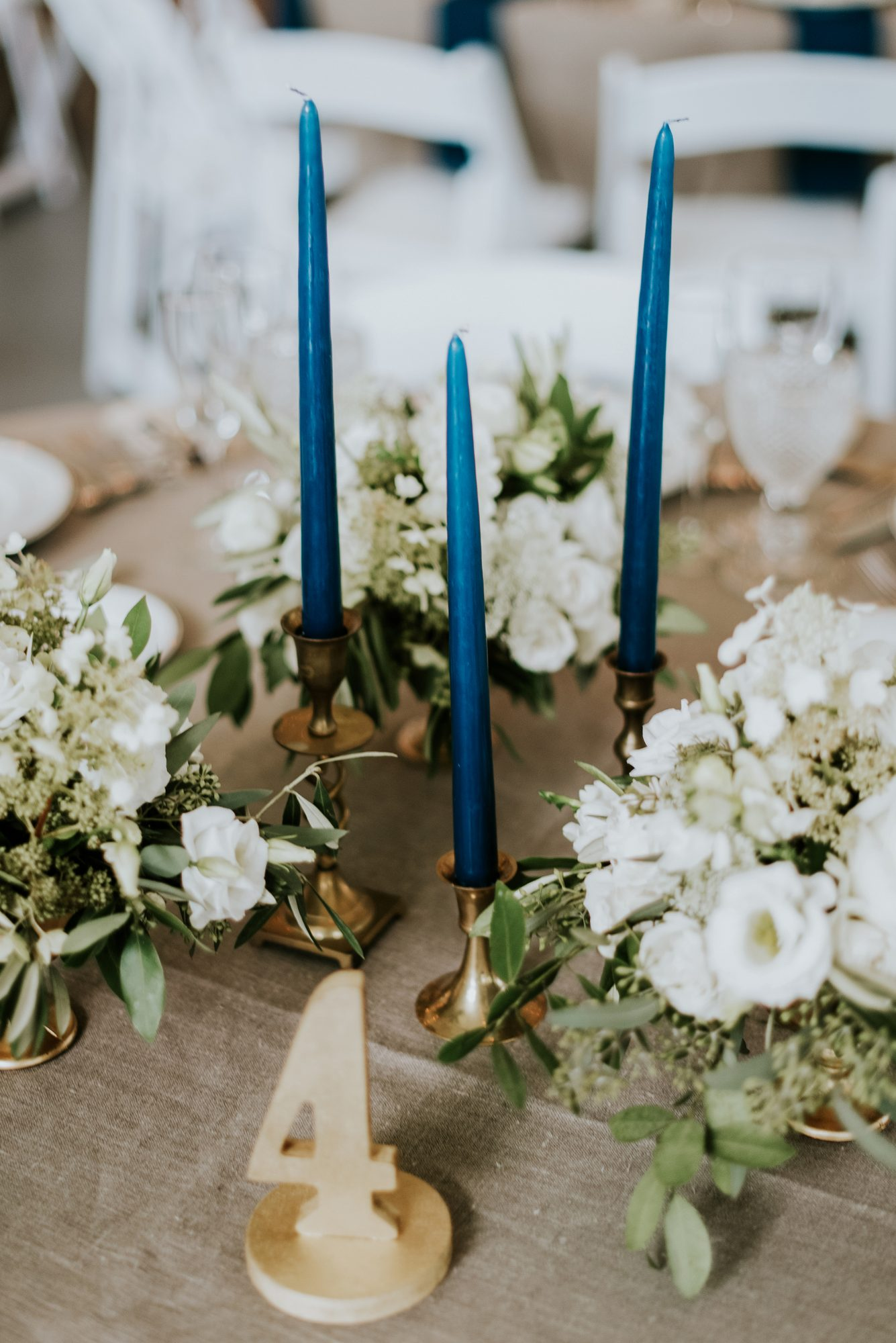cluster centerpiece with blue candles and white flowers