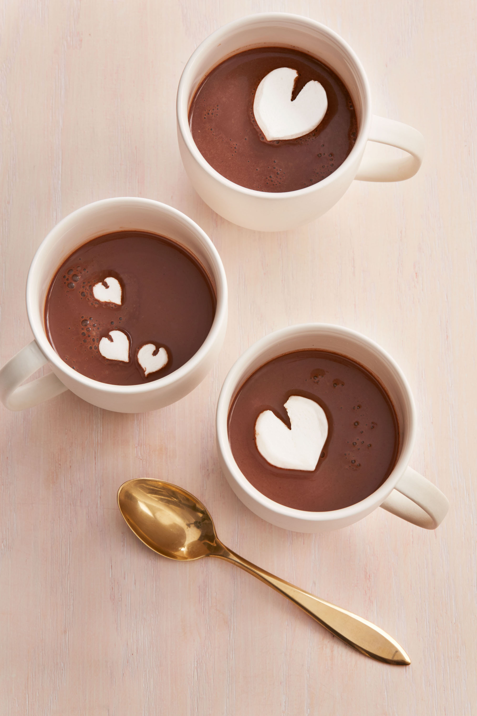 three mugs of hot cocoa with heart-shaped marshmallows
