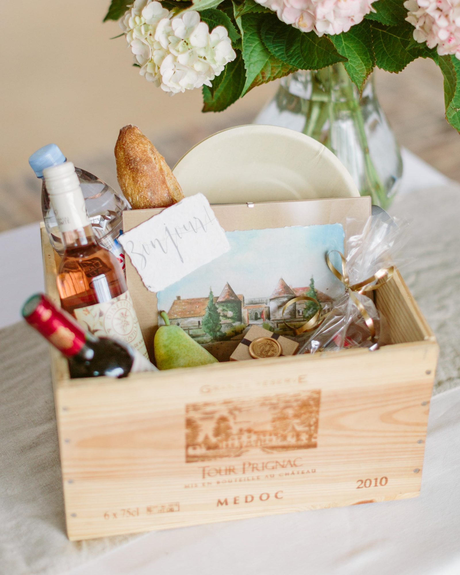 Upon arrival, guests received a French wine crate filled with quintessential goodies from Paris. Each box held the fixings for a traditional Parisian picnic including wine, baguettes, cheese pairings, jam, a pear, and disposable wooden plates and cutlery. An illustration of the venue by the mother-of-the-bride, served as a beautiful memory. In addition, guests were surprised at turndown service in their guest rooms, when small, sealed boxes (like the one pictured above) adorned each pillow with a thank-you note. Inside the boxes were Anne-Claire's favorite French chocolates—Maxim's Chocolate!
