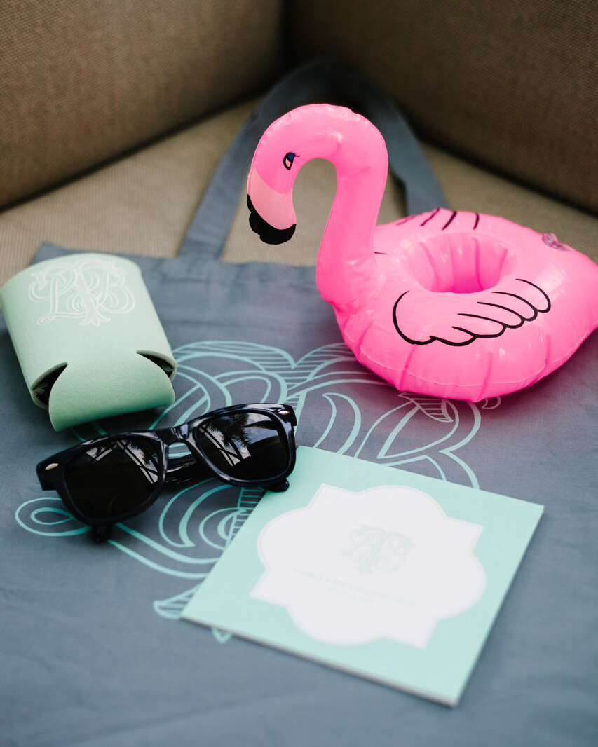 Help attendees enjoy their poolside stay with thematic wedding favors. This couple handed out Custom Ink totes filled with Custom Ink koozies, Discount Mugs sunglasses, and Urban Outfitters drink floats. Many of the items were adorned with their Alison R. Banks Designs monogram.