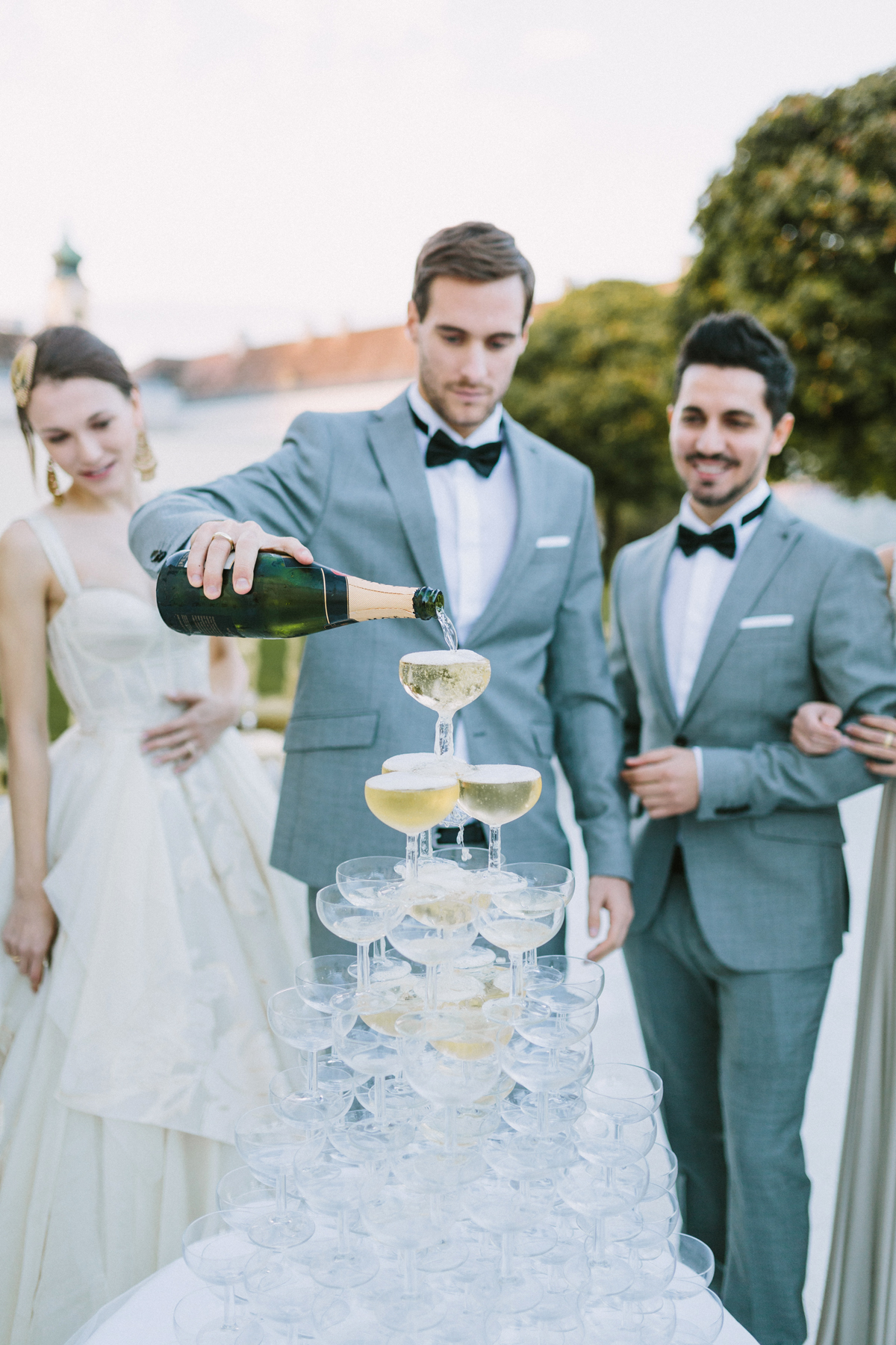 wedding champagne towers groom pours champagne