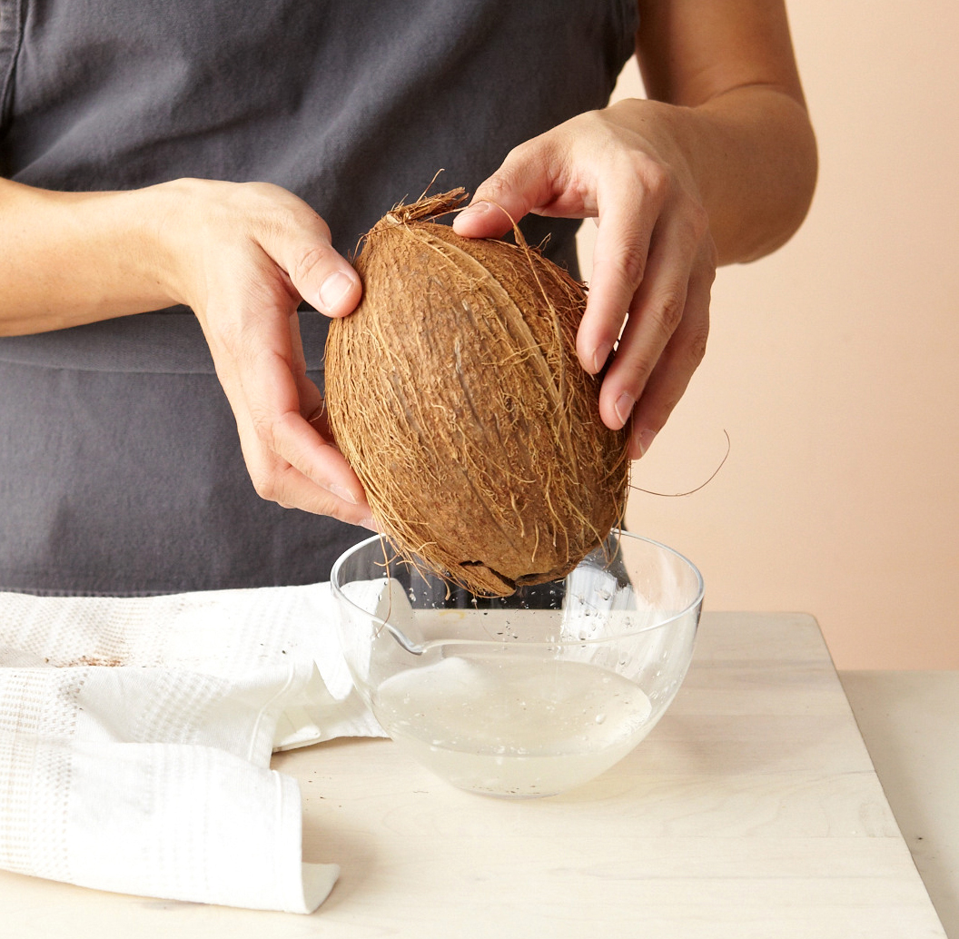 hands holding coconut bowl water