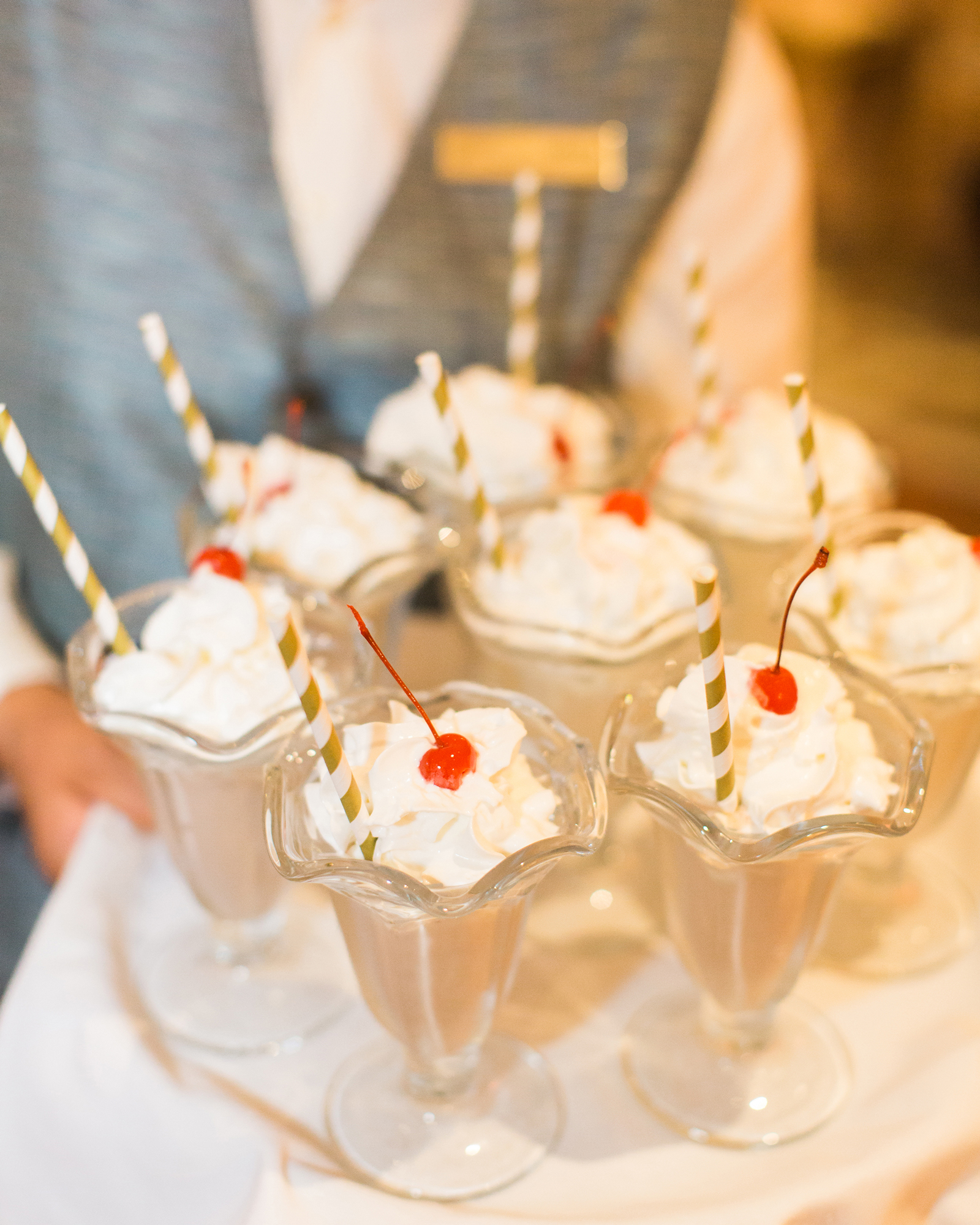 milkshakes topped with whipped cream and a cherry served on a tray