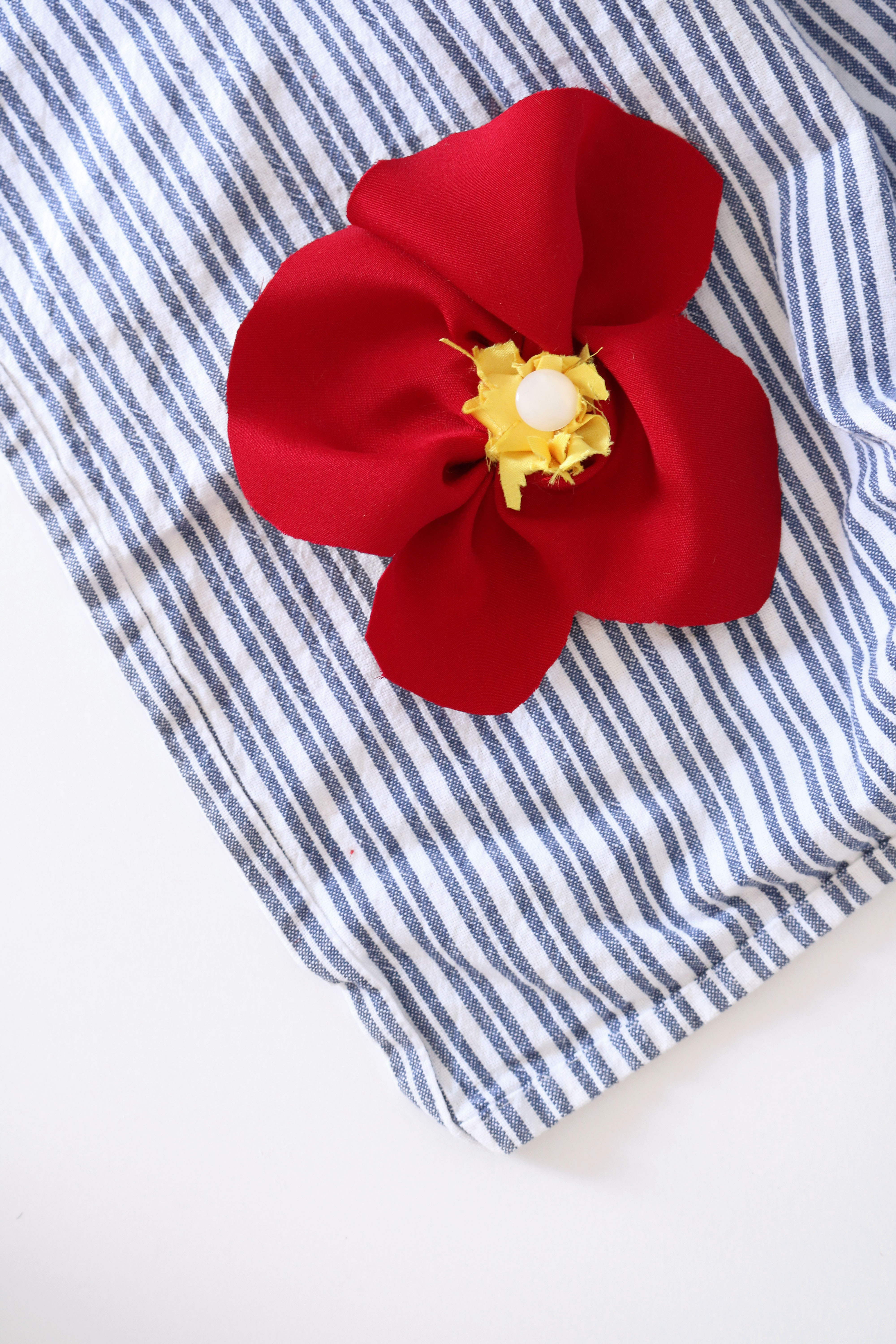 red silk remembrance poppy on blue striped towel