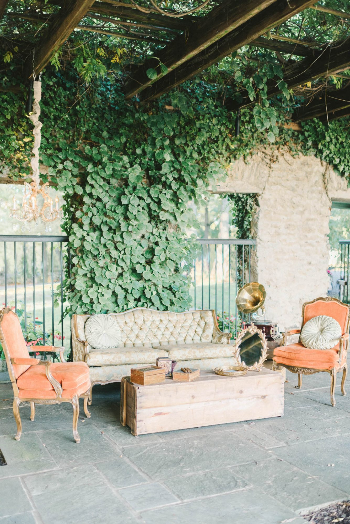 wedding lounge orange and tan seating and greenery wall