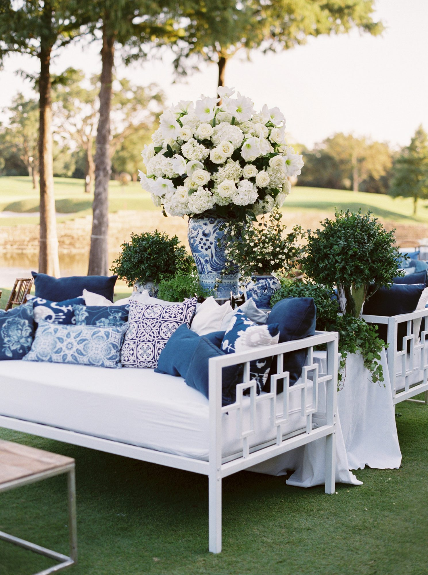 wedding lounge white couches with blue pillows outdoors