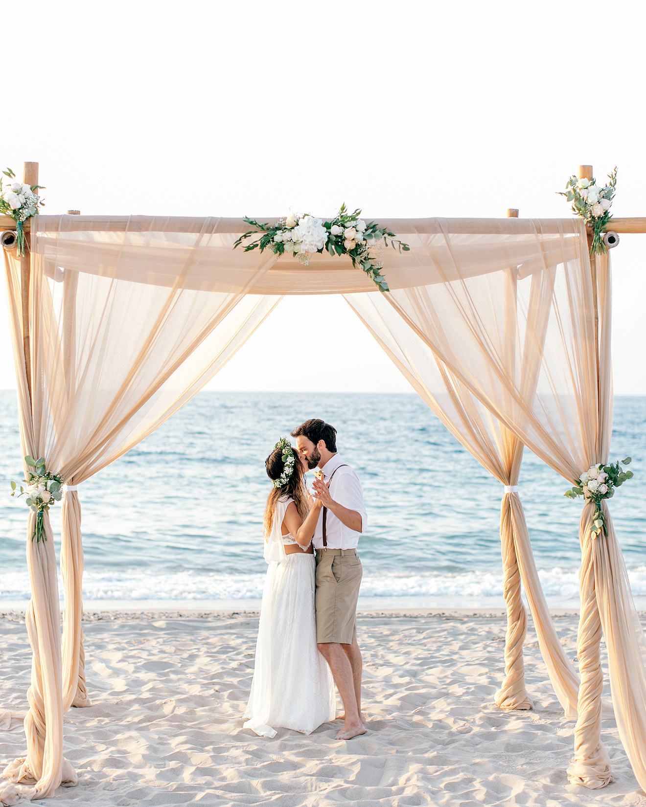 newlyweds kissing under tulle-wrapped structure
