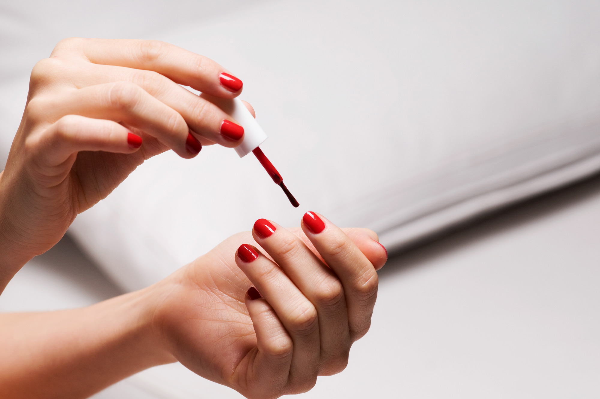 woman painting nails red nail polish