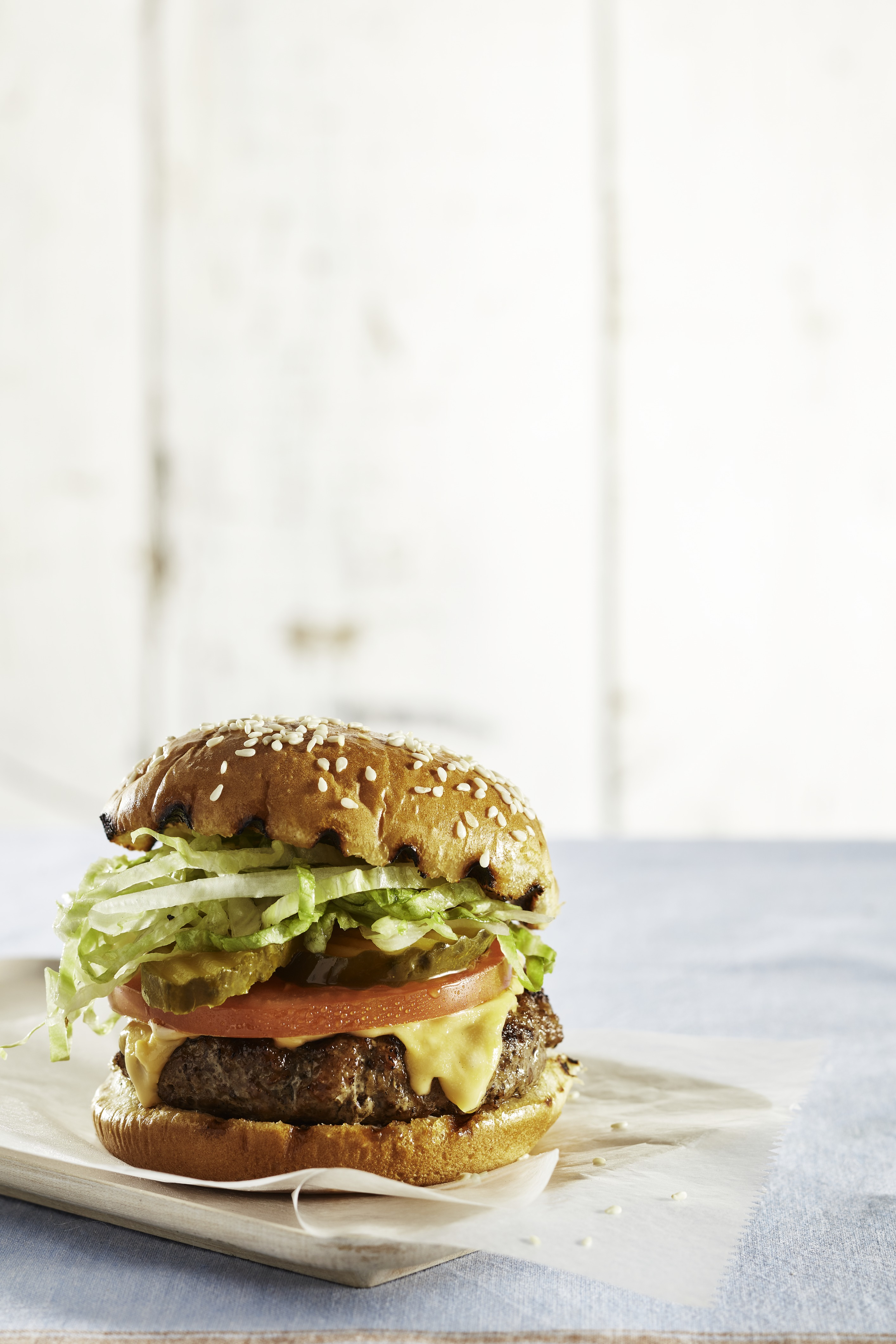 cheeseburger with grilled bun tomatoes pickles lettuce