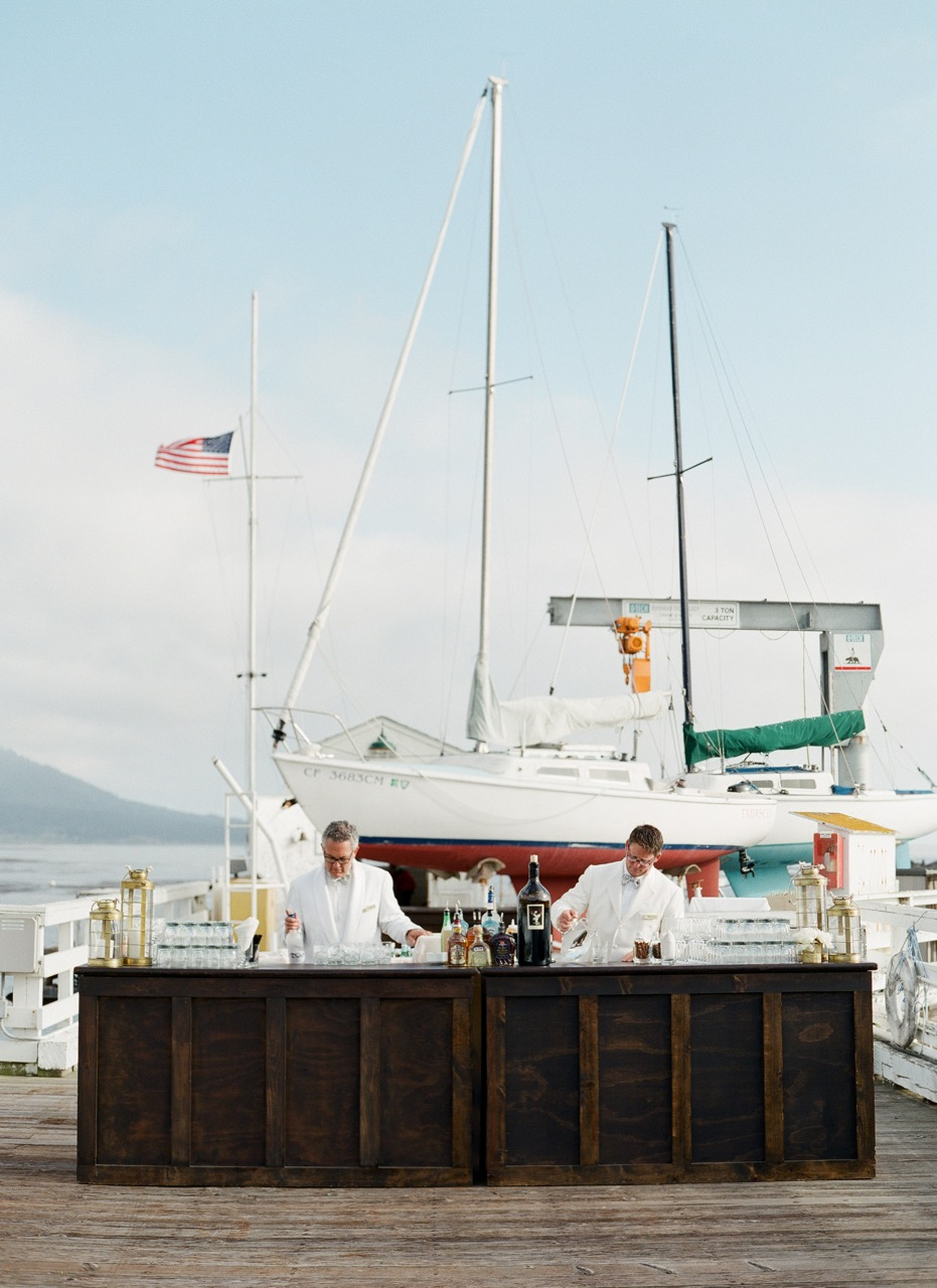 bartenders at bar on dock in front of boat