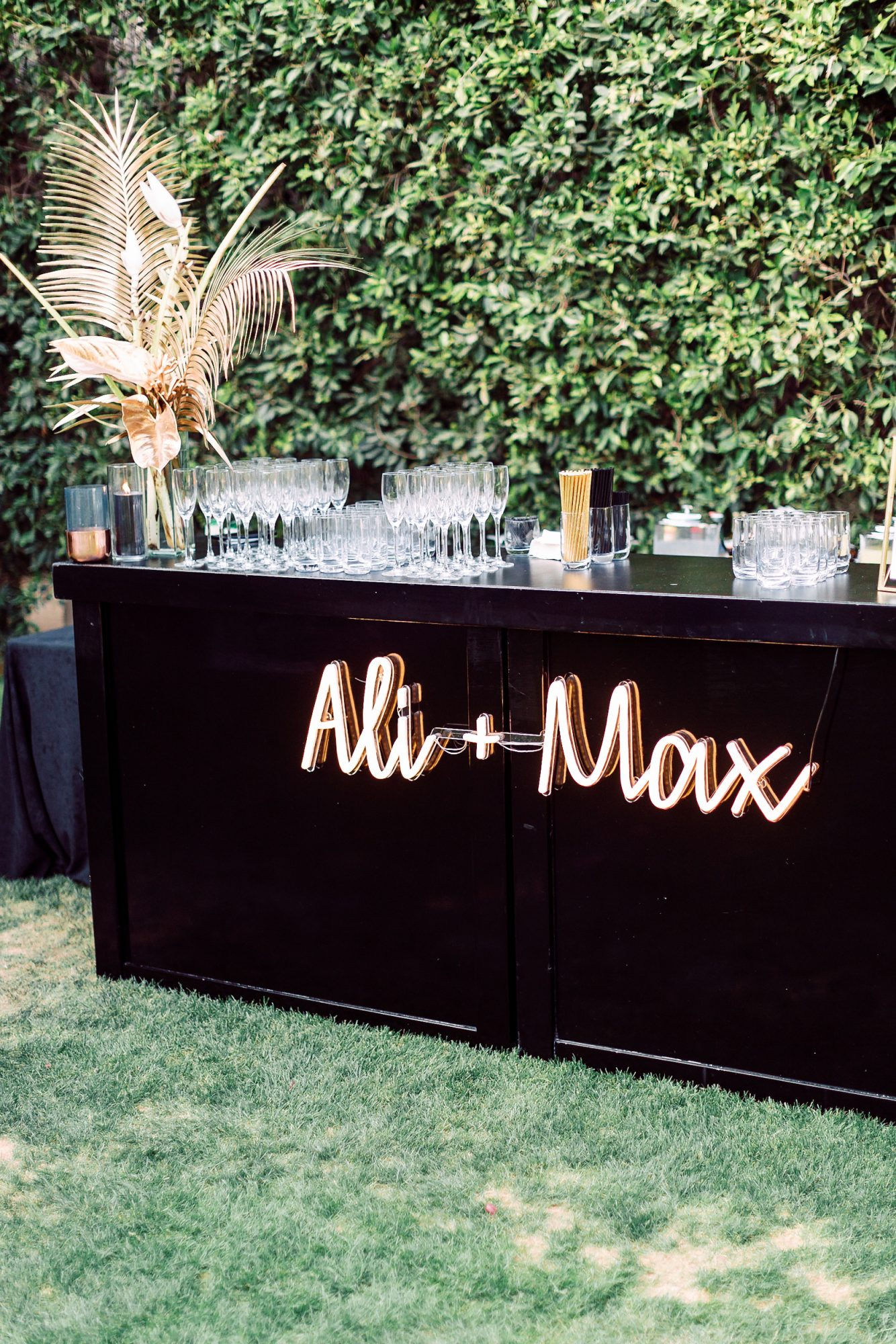 ali + max neon sign on outdoor bar