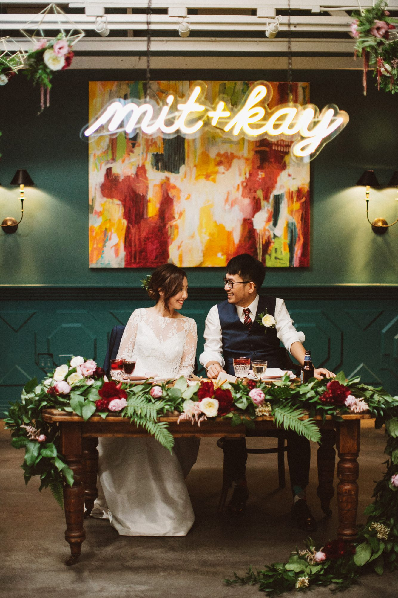 mit + kay neon sign behind sweetheart table with couple