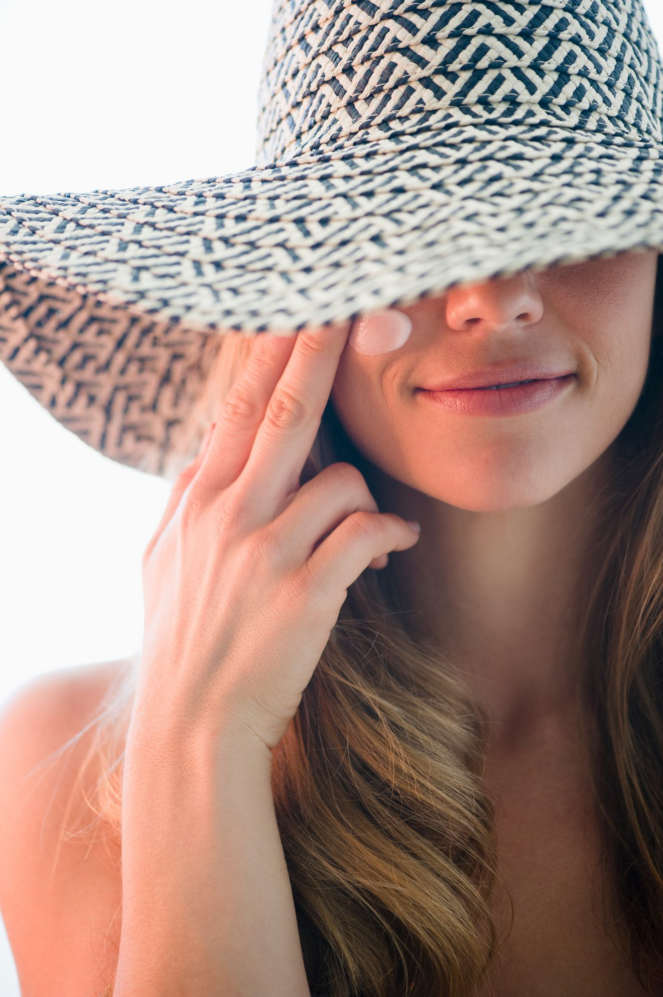 Woman Wearing Sunscreen and Sun Hat