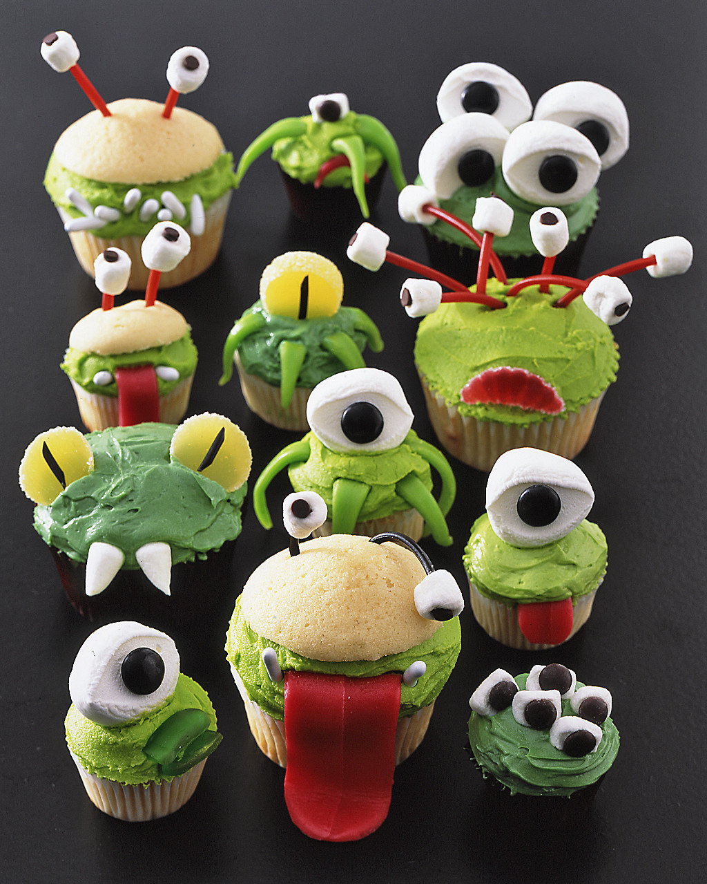 Let your imaginations (and fears) run wild this Halloween. We're serving up bewildering and straight up bizarre Halloween cupcake recipes for a kid-friendly party or a grown-up bash. From monsters to creepy crawlers and things that come alive, you can decorate these cupcakes in a way that's totally terrifying. When it comes to our favorite black and orange holiday, we've got more than a few tricks up our sleeves.If you're throwing a Halloween party for kids, a cupcake decorating station is an activity that will keep them occupied for hours (and give them the jitters, too). Start with a base recipe for your Halloween cupcakes—basic vanilla, chocolate, chocolate chip cookie, and red velvet (just to name a few!). Next, fill the cupcakes with a spooky surprise filling, like orange curd, chocolate mousse, or lighter peanut butter frosting. For an added layer of fun, don't reveal what's on the inside and wait for guests to take a bewitching bite.Finally, set out bowls with candy galore for decorating. With these frightful cupcakes, you'll need lots of black licorice, green and black food coloring, taffy, jelly beans, gummy rings, marshmallows, and mini chocolate chips. Kids will cackle with delight as they get to create their very own Frankenstein with sugary candy and brightly colored frosting. Things may get messy, but that's half the fun.Use the recipes in this collection for spooky inspiration and you'll be amazed at the Halloween creations kids will come up with. This is a day no one should skip the treats (though there will certainly be plenty of tricks, too). Be consumed by the eerie and edible, the flavorful and the frightful. Our Halloween cupcake recipes will satisfy everyone's dark side.