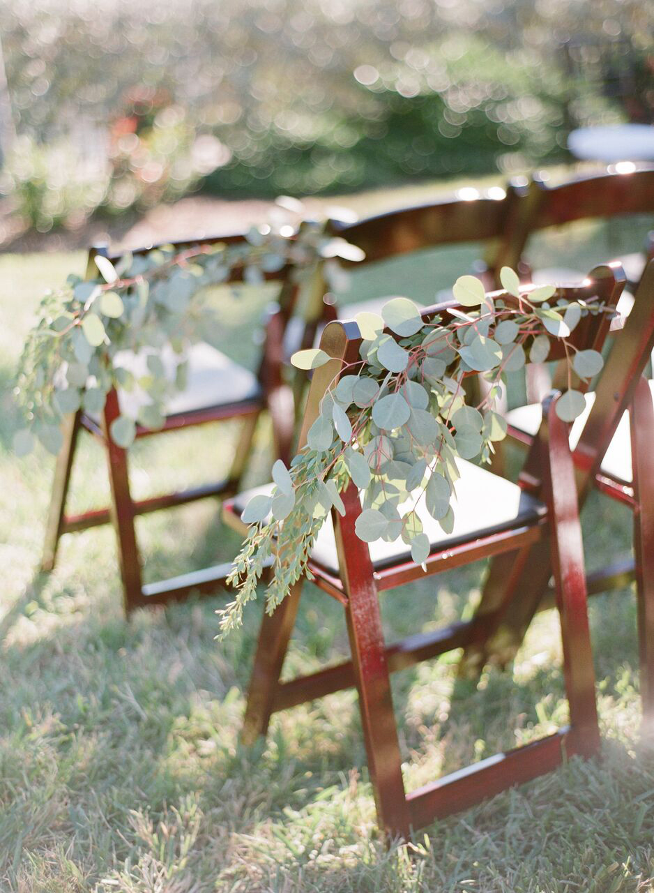 green leaf vines decorating back of wood chairs
