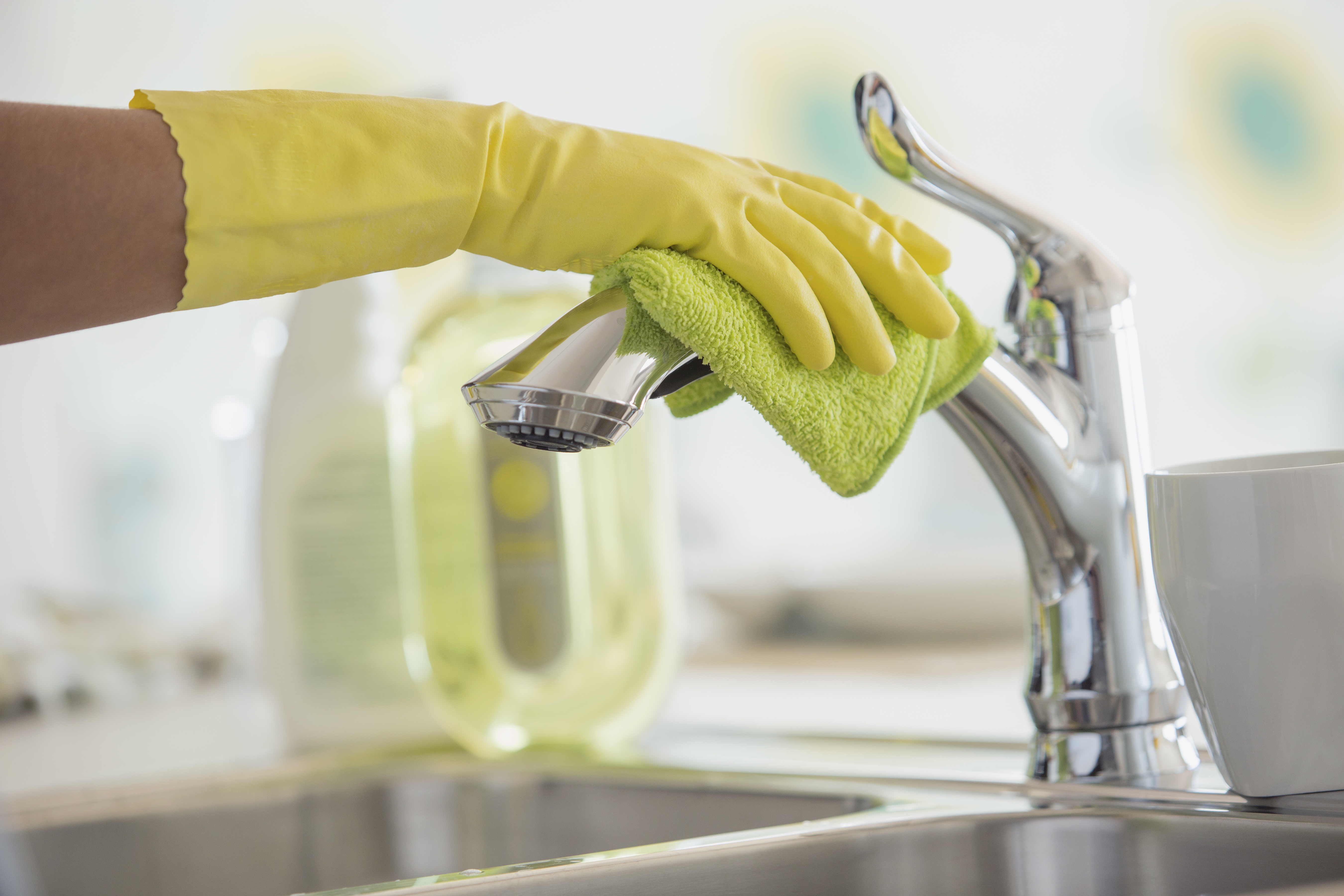 Woman cleaning kitchen faucet with gloves on.