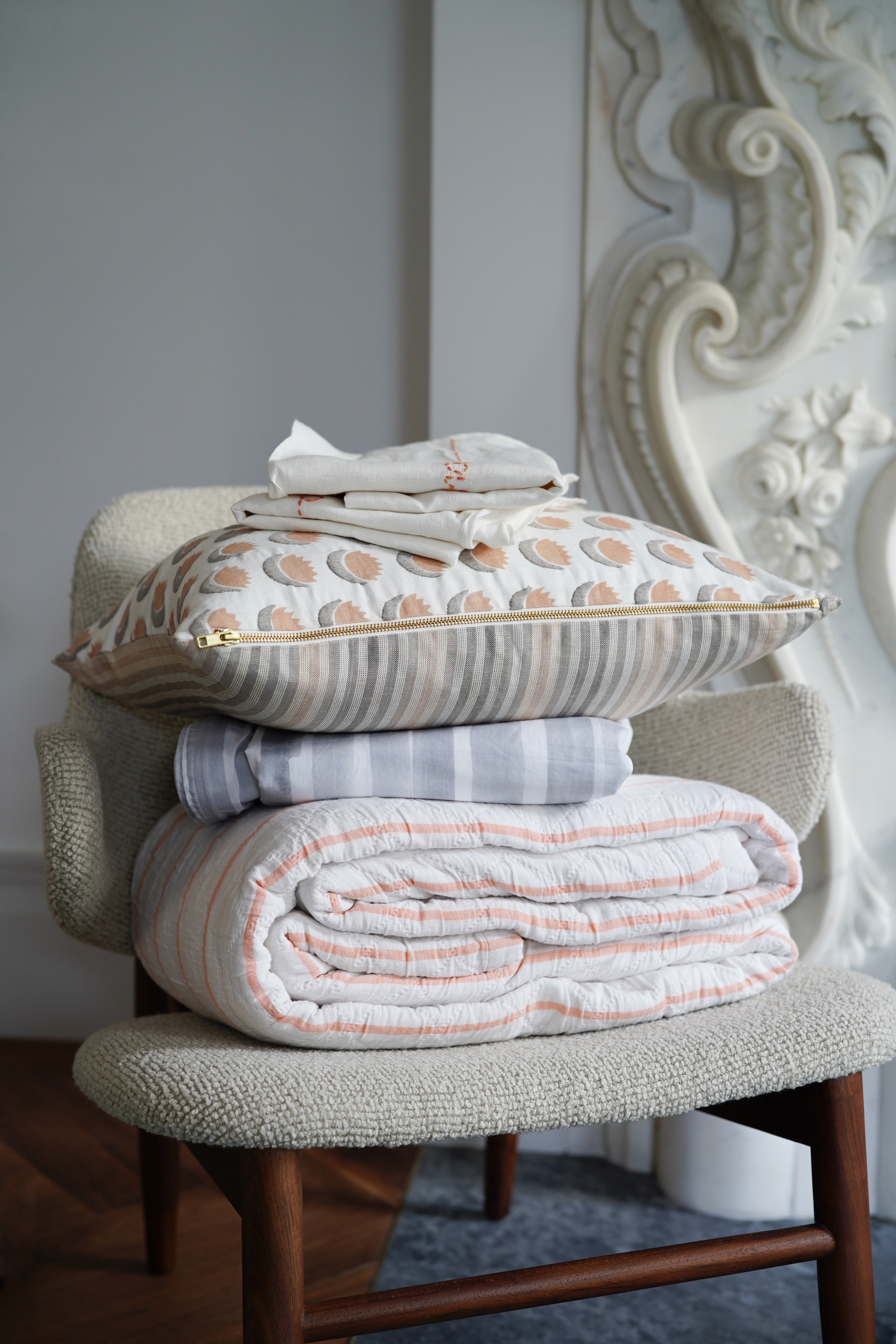 Rebecca Atwood bedding stacked on a chair
