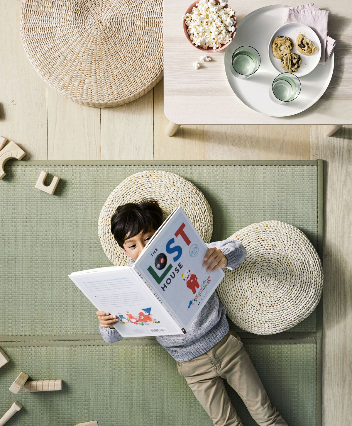 boy laying on floor reading a book