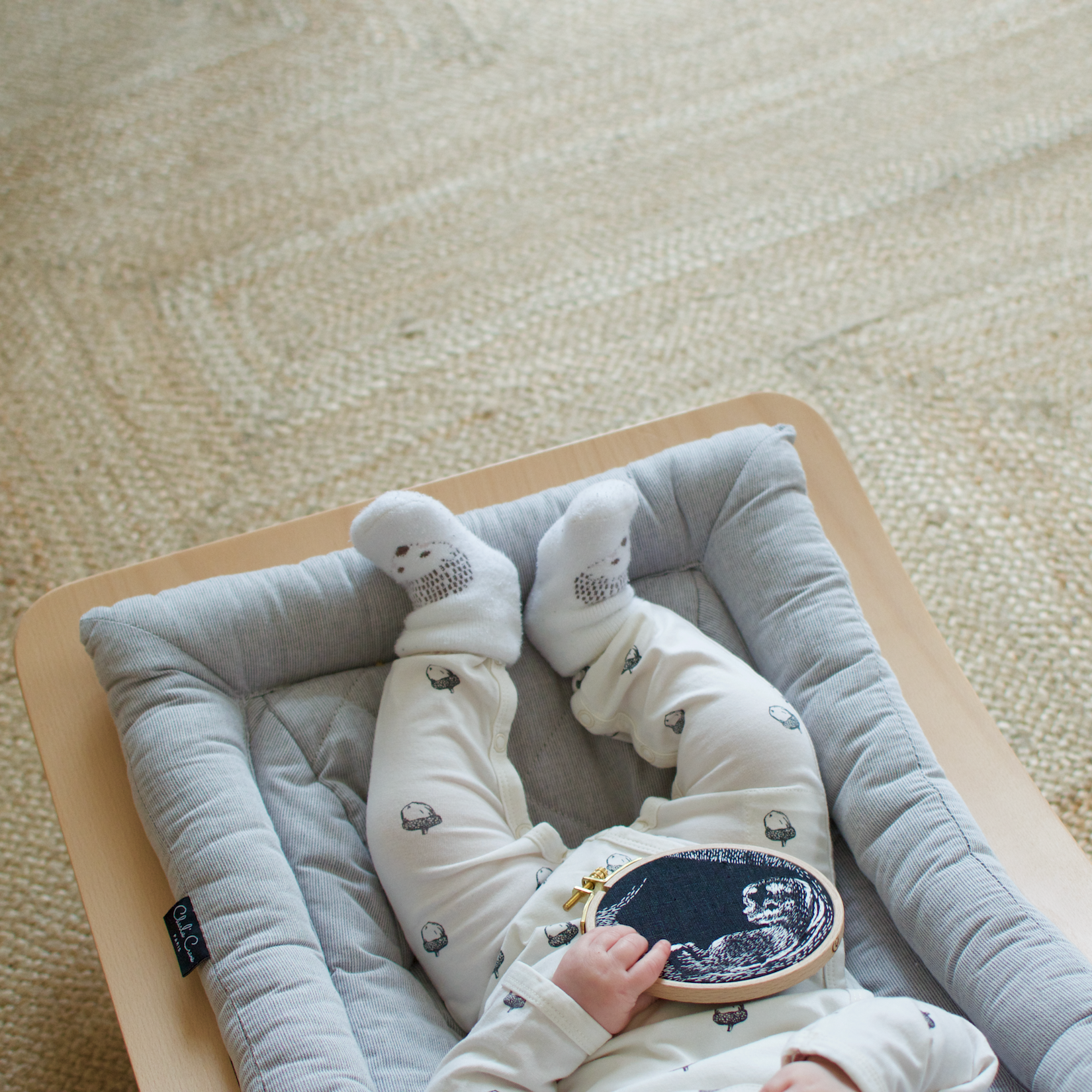 A baby holds an embroidery hoop with a sonogram embroidered on it.