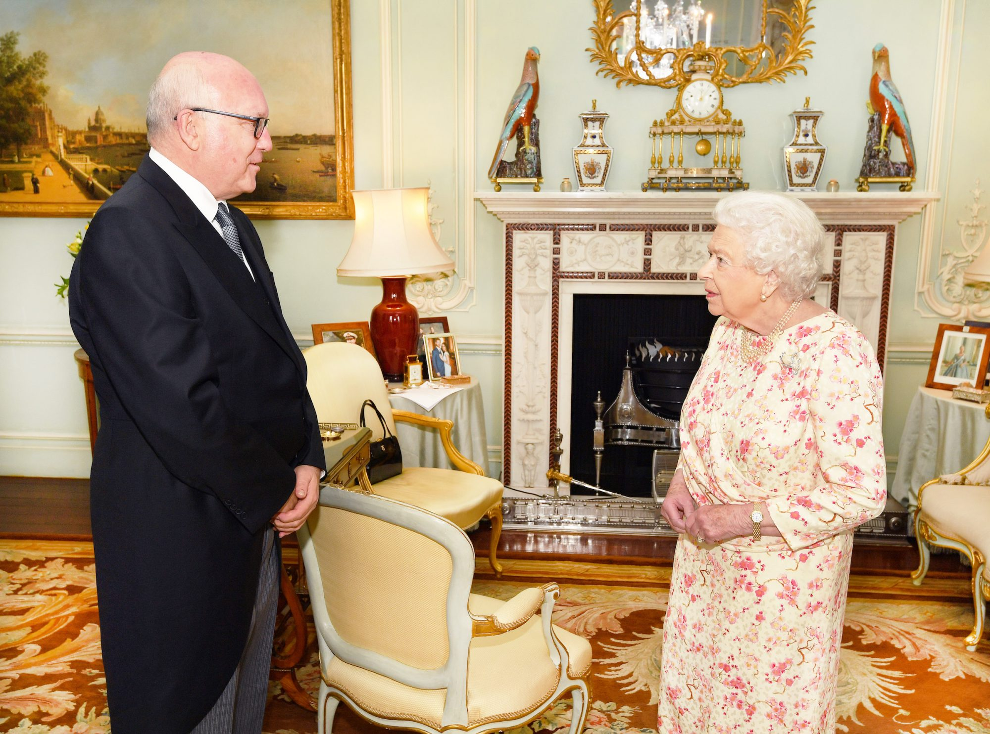 queen elizabeth ii with photo of prince harry and meghan markle in background