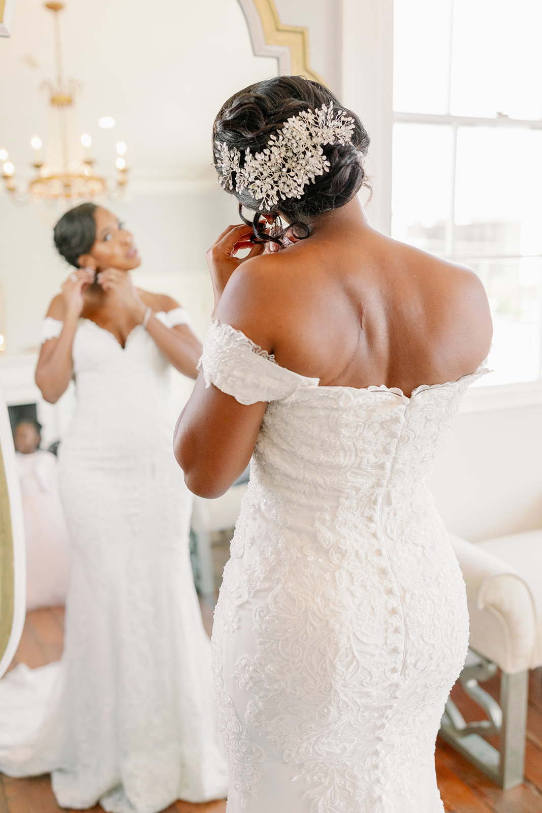 Bride wearing a slightly fitted, lace, off-the-shoulder gown