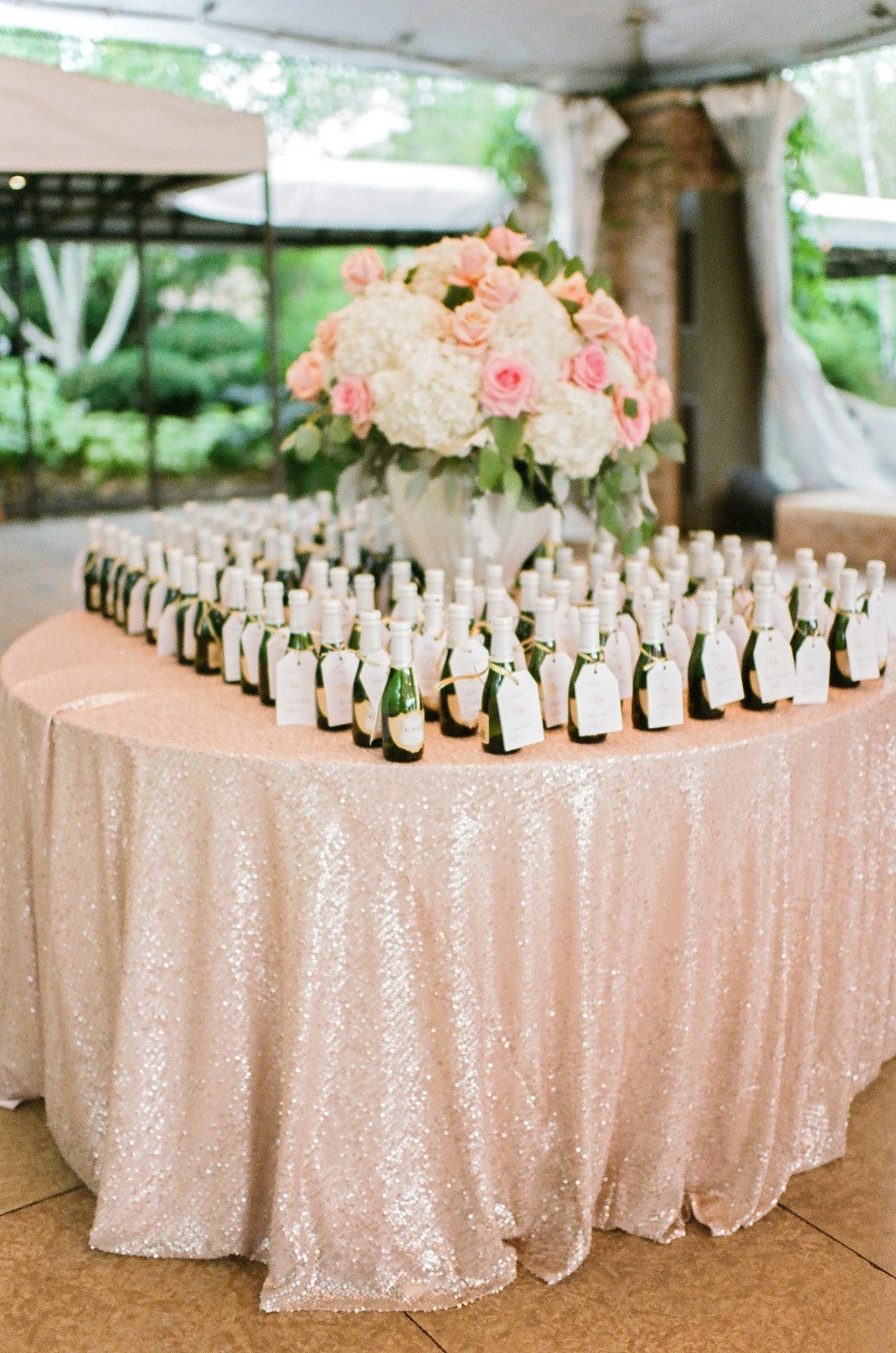 alcohol escort cards mini champagne bottles on round table